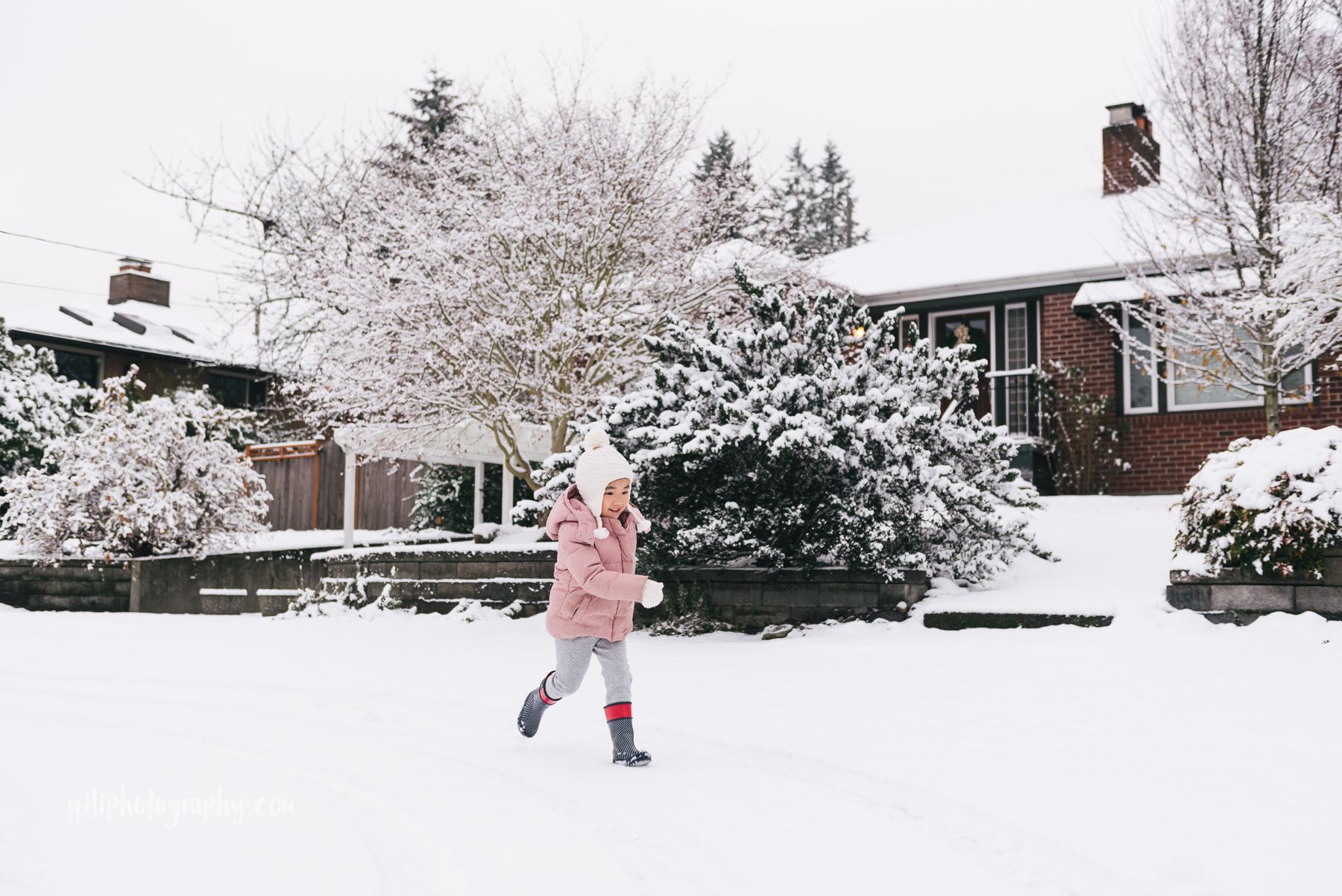little girl running in snow seattle