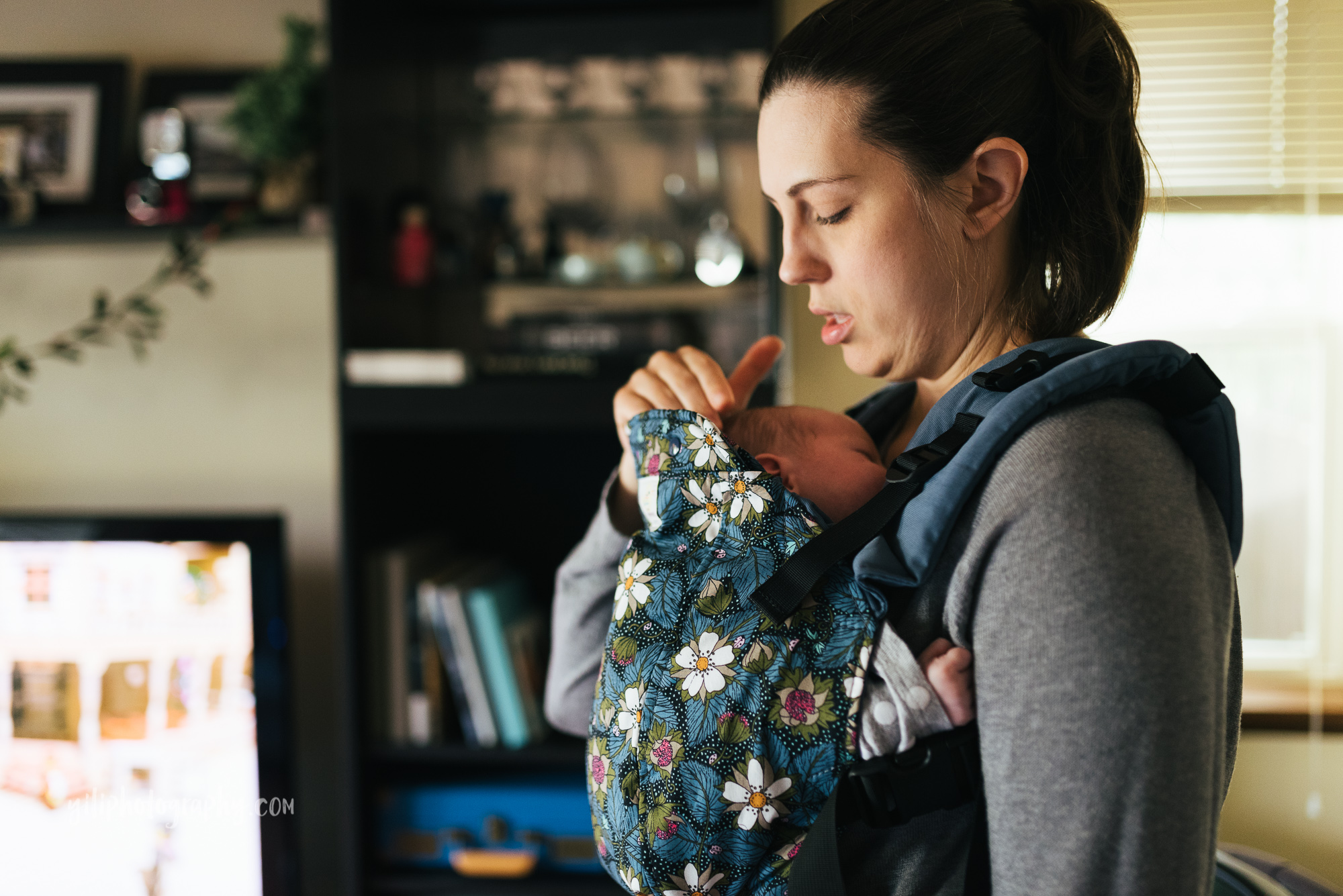 seattle mom adjusting newborn baby in baby carrier