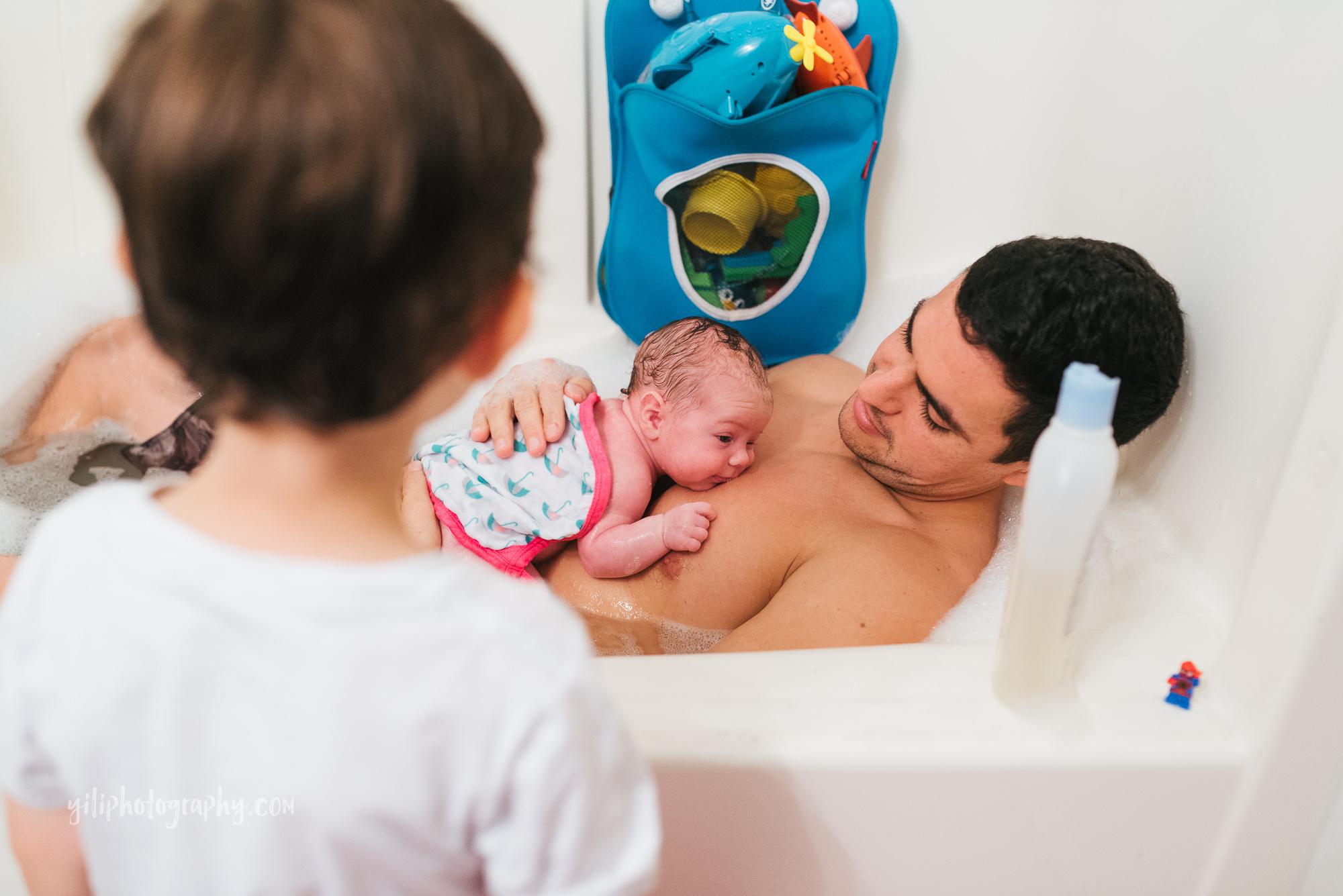 seattle newborn baby lying on dad's chest in bathtub