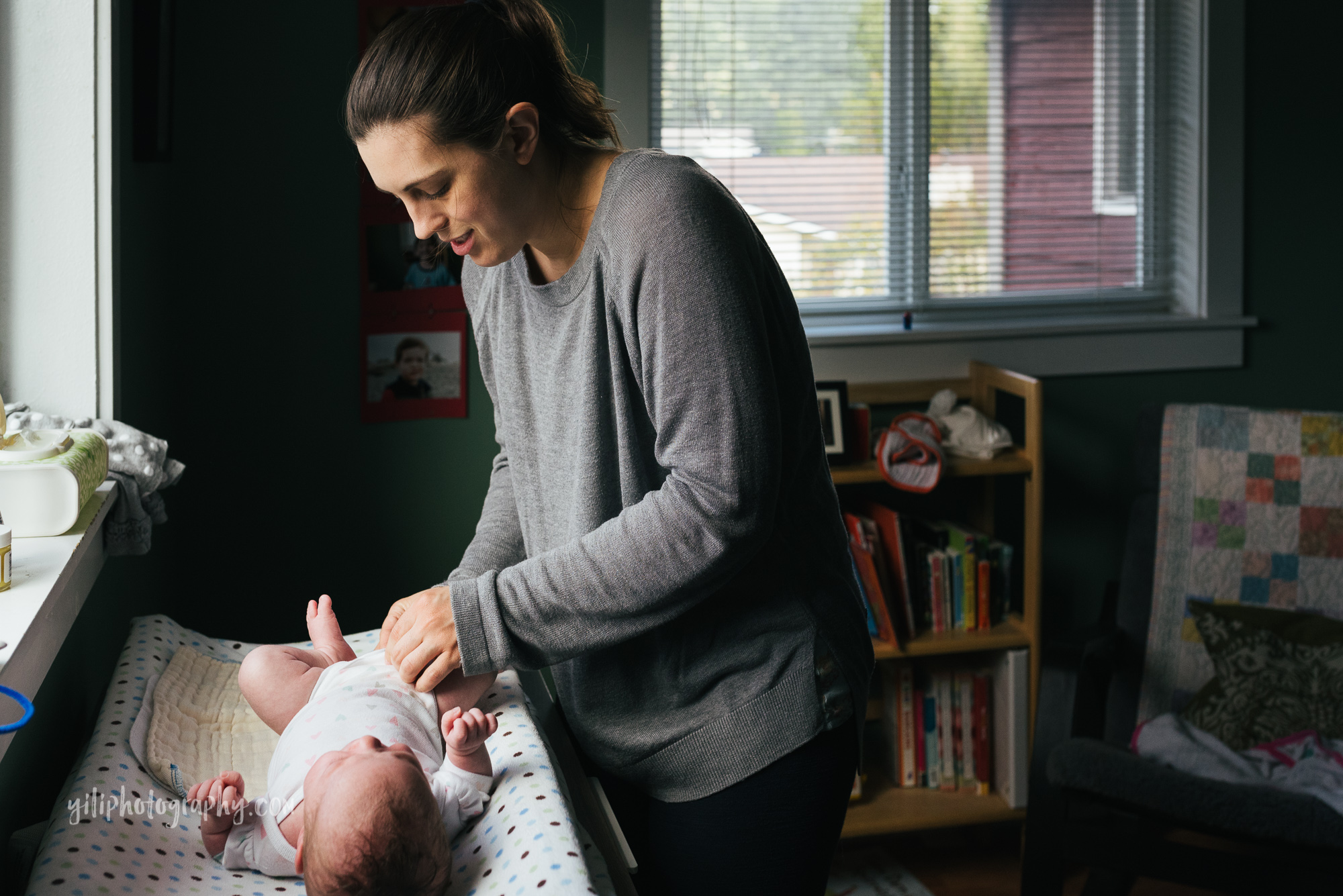 seattle mom smiling while she changes baby