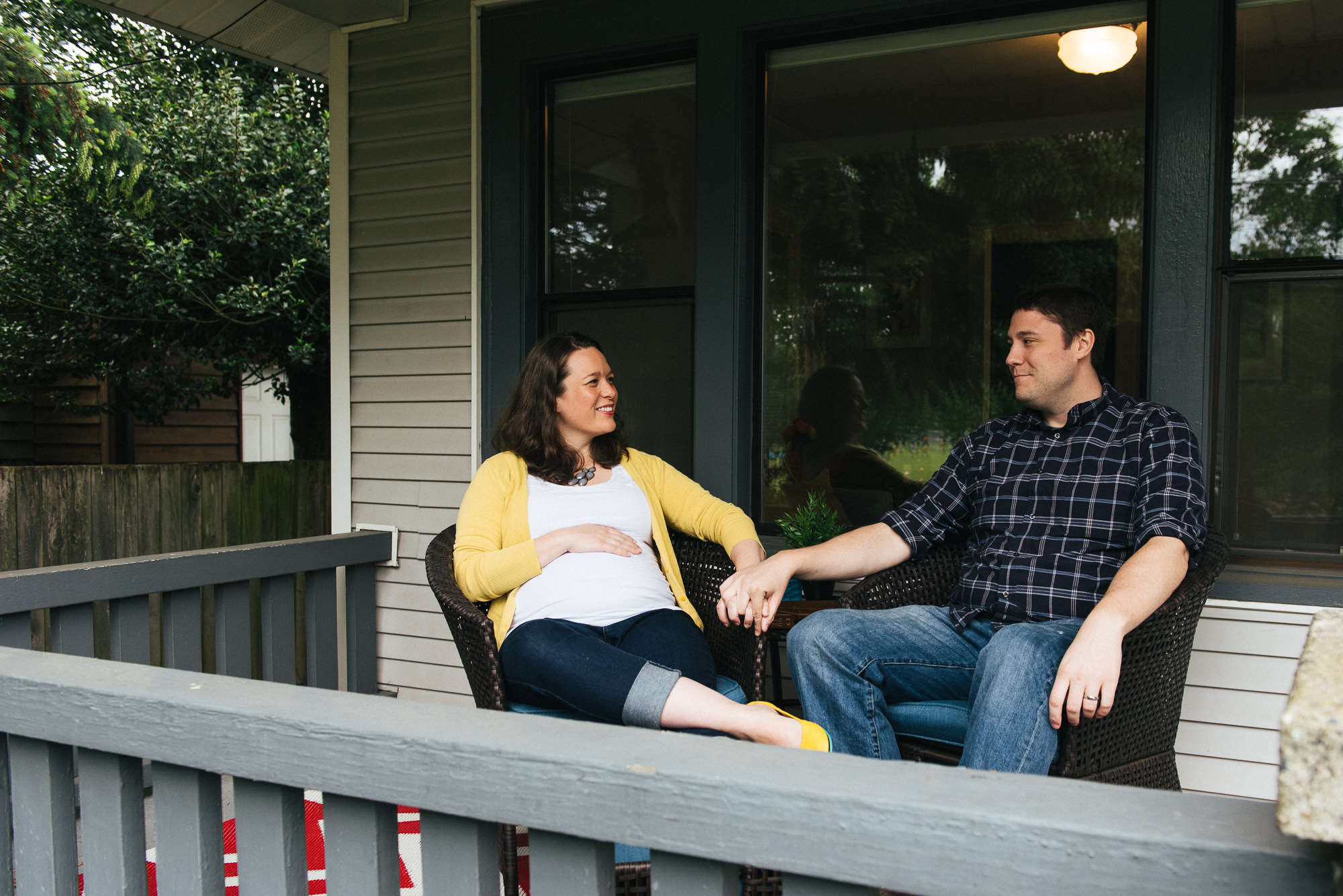 Expecting wife sitting on porch with husband