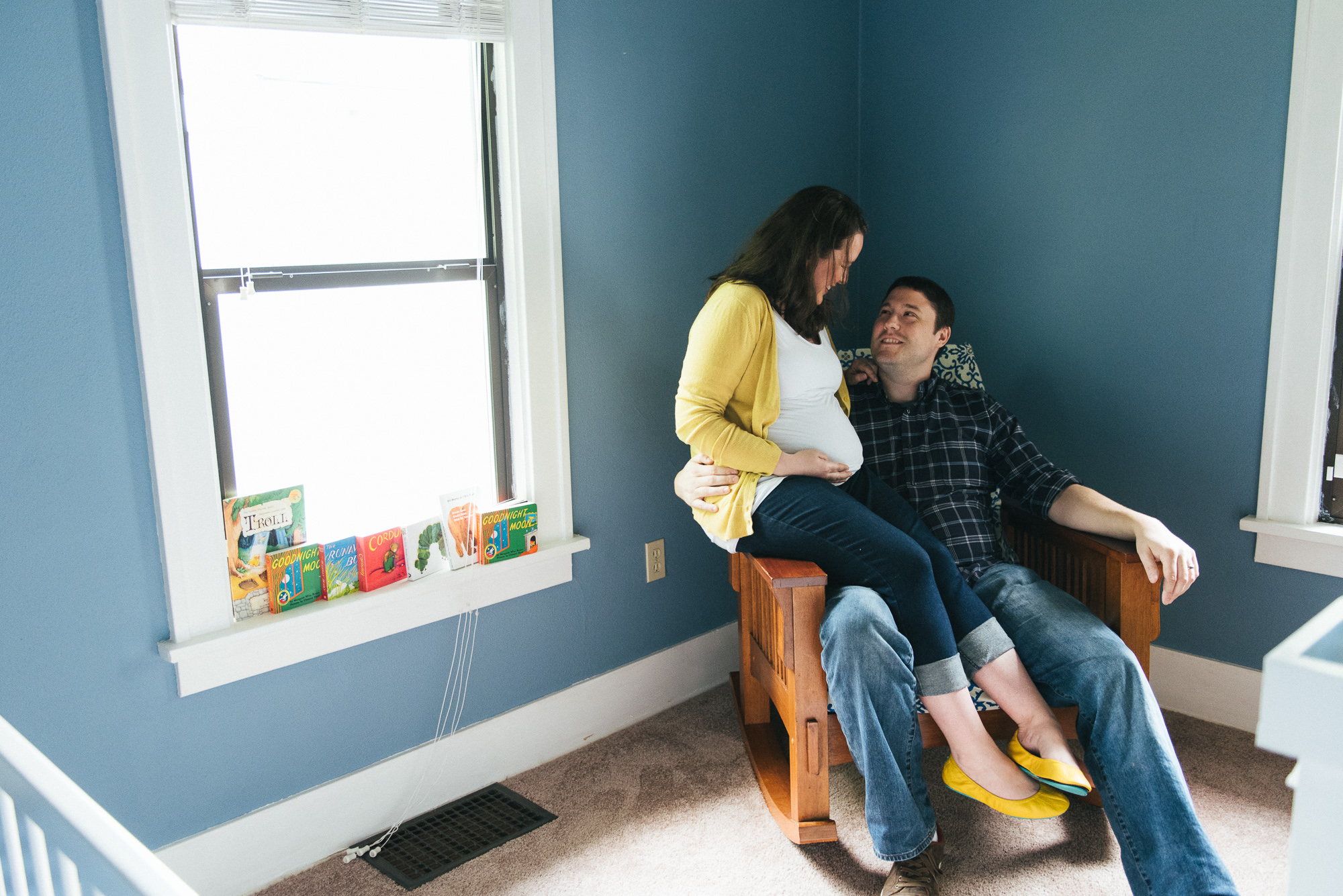 Expecting couple sitting together in baby nursery