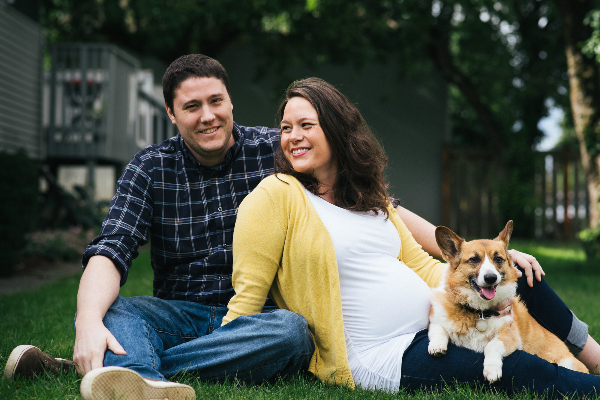 expecting couple sitting in yard with dog