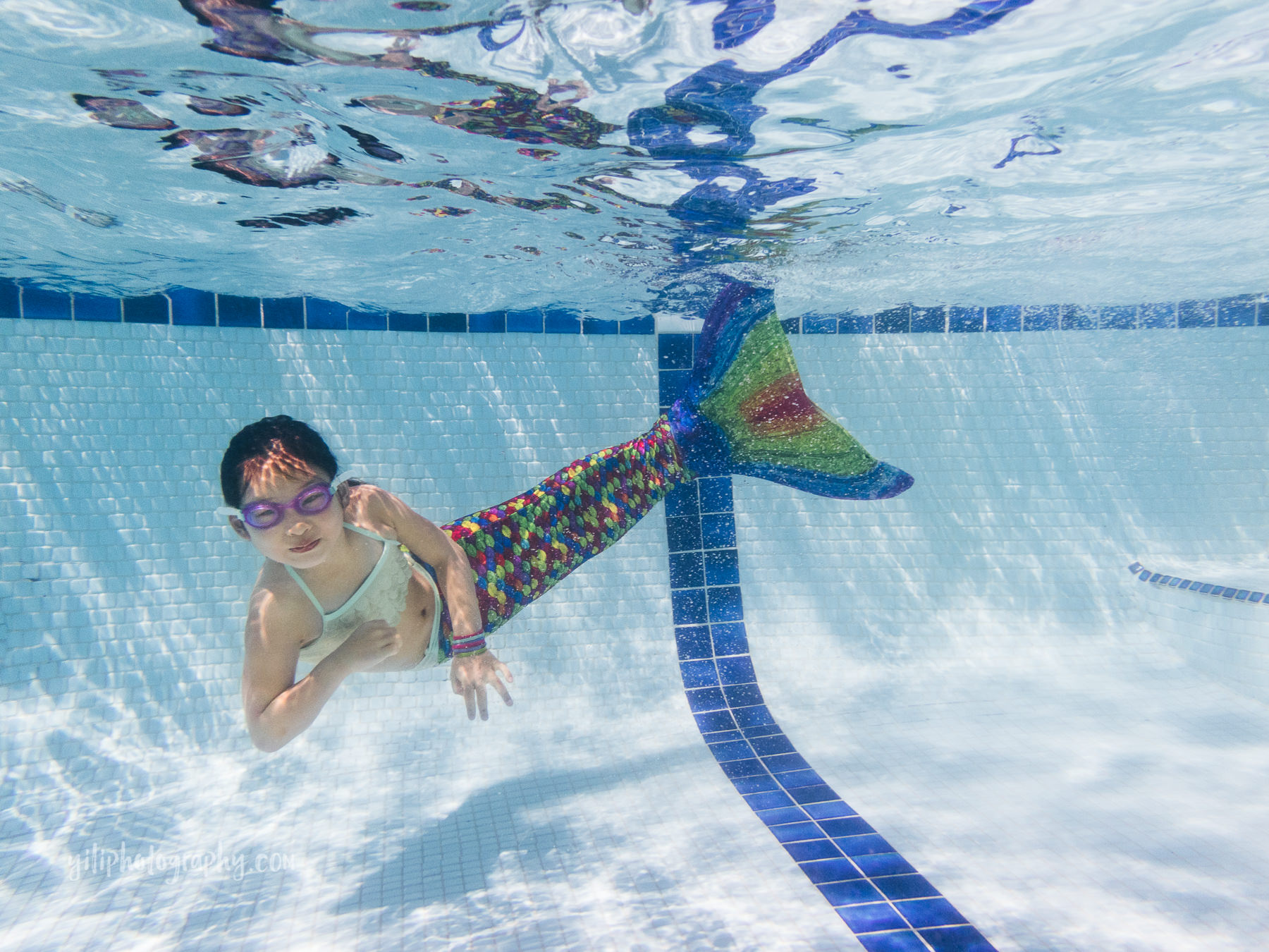 girl posing underwater in mermaid tail