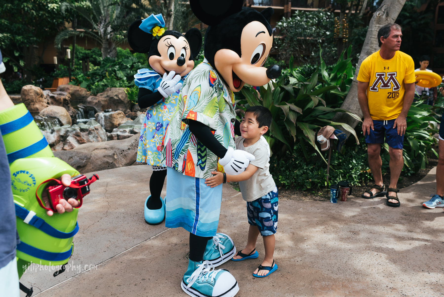 little boy gives mickey a hug at aulani
