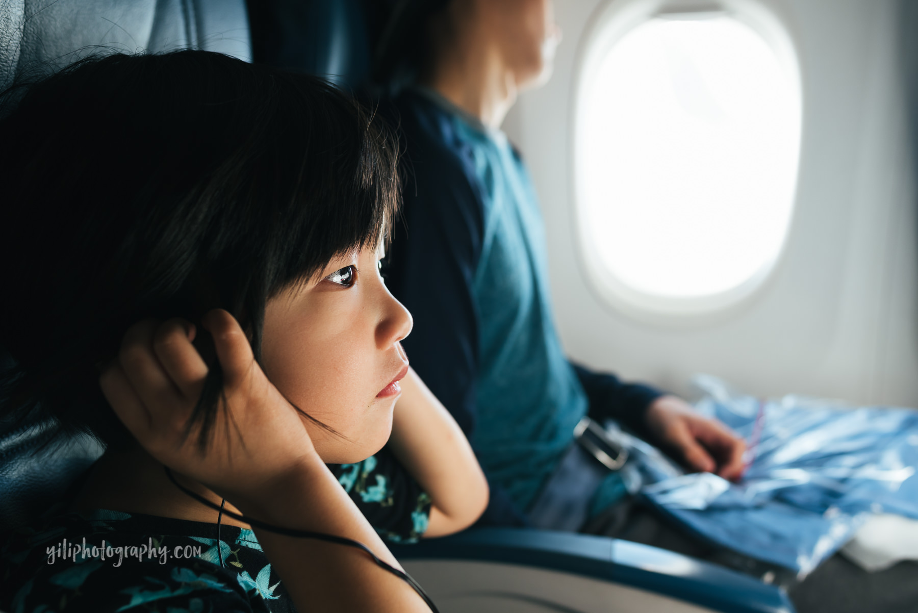little girl on airplane holding headphones
