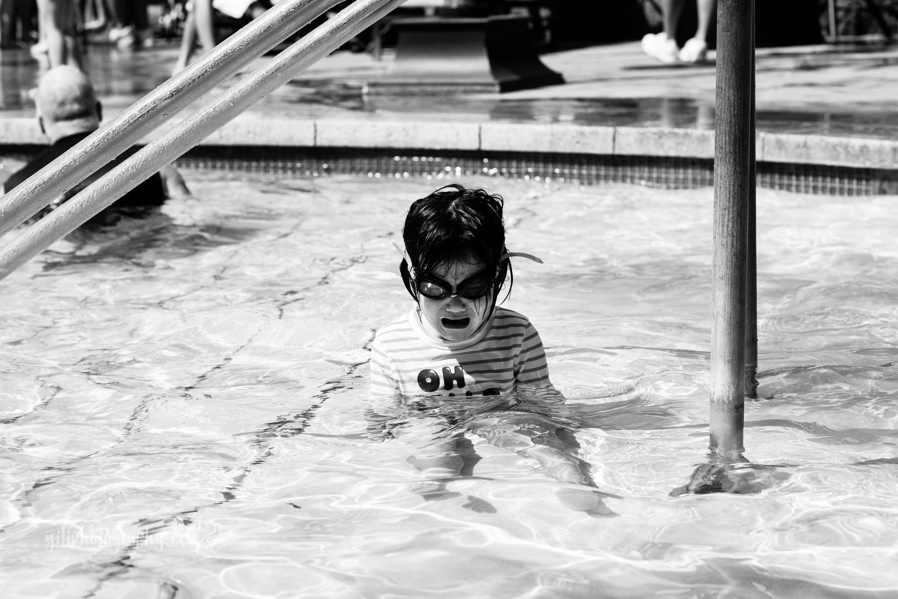black and white photo of toddler girl having tantrum in pool