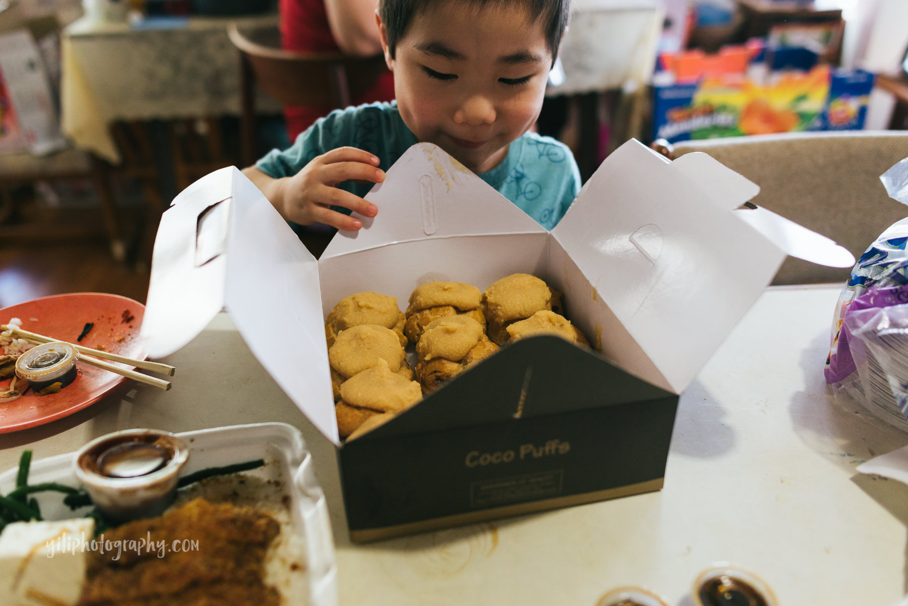 boy looking into box of cream puffs