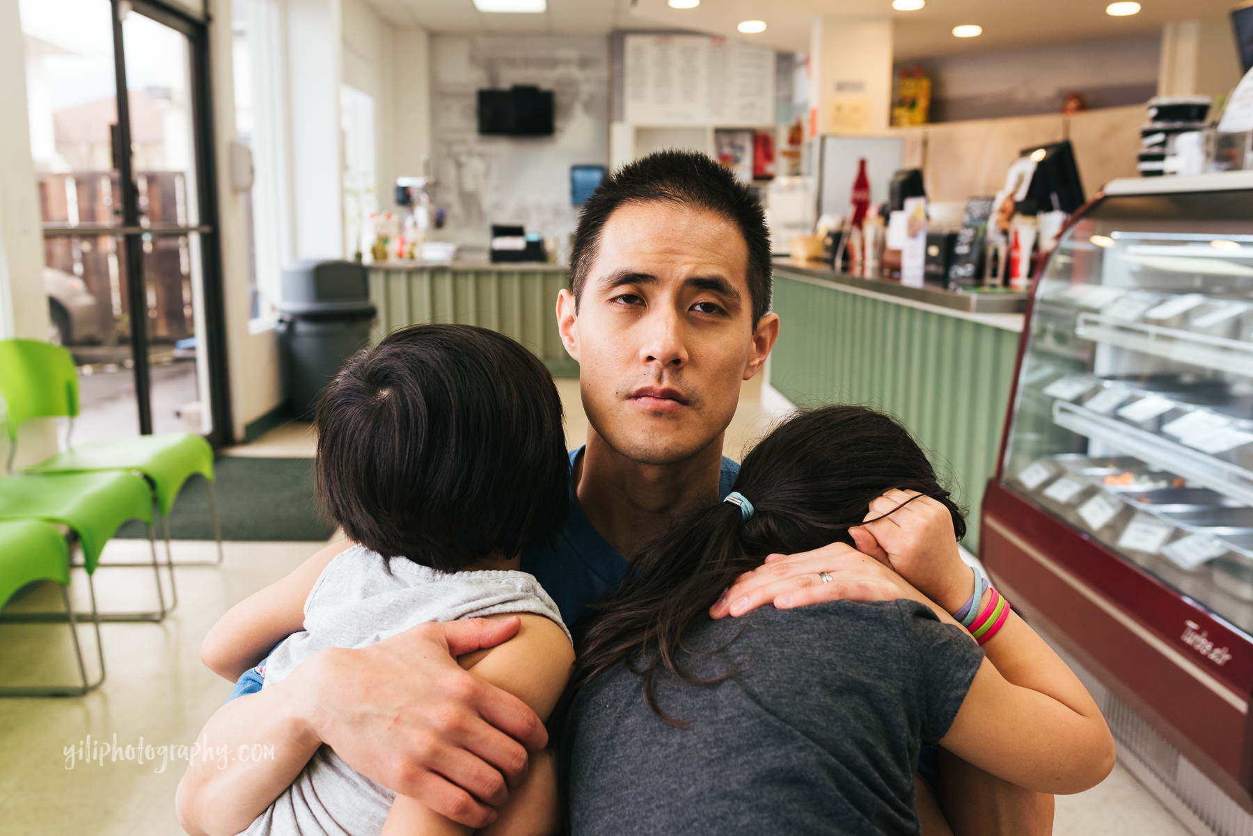 tired father hugging two daughters