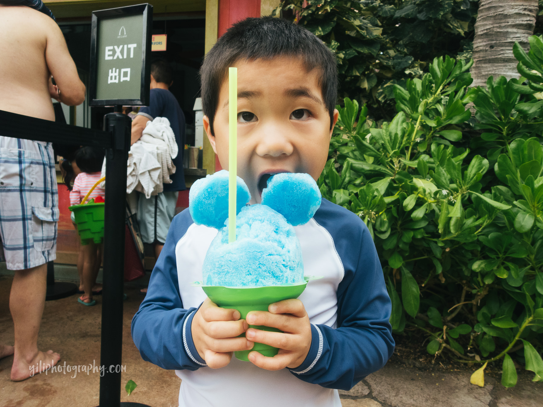 boy biting shave ice with mickey ears