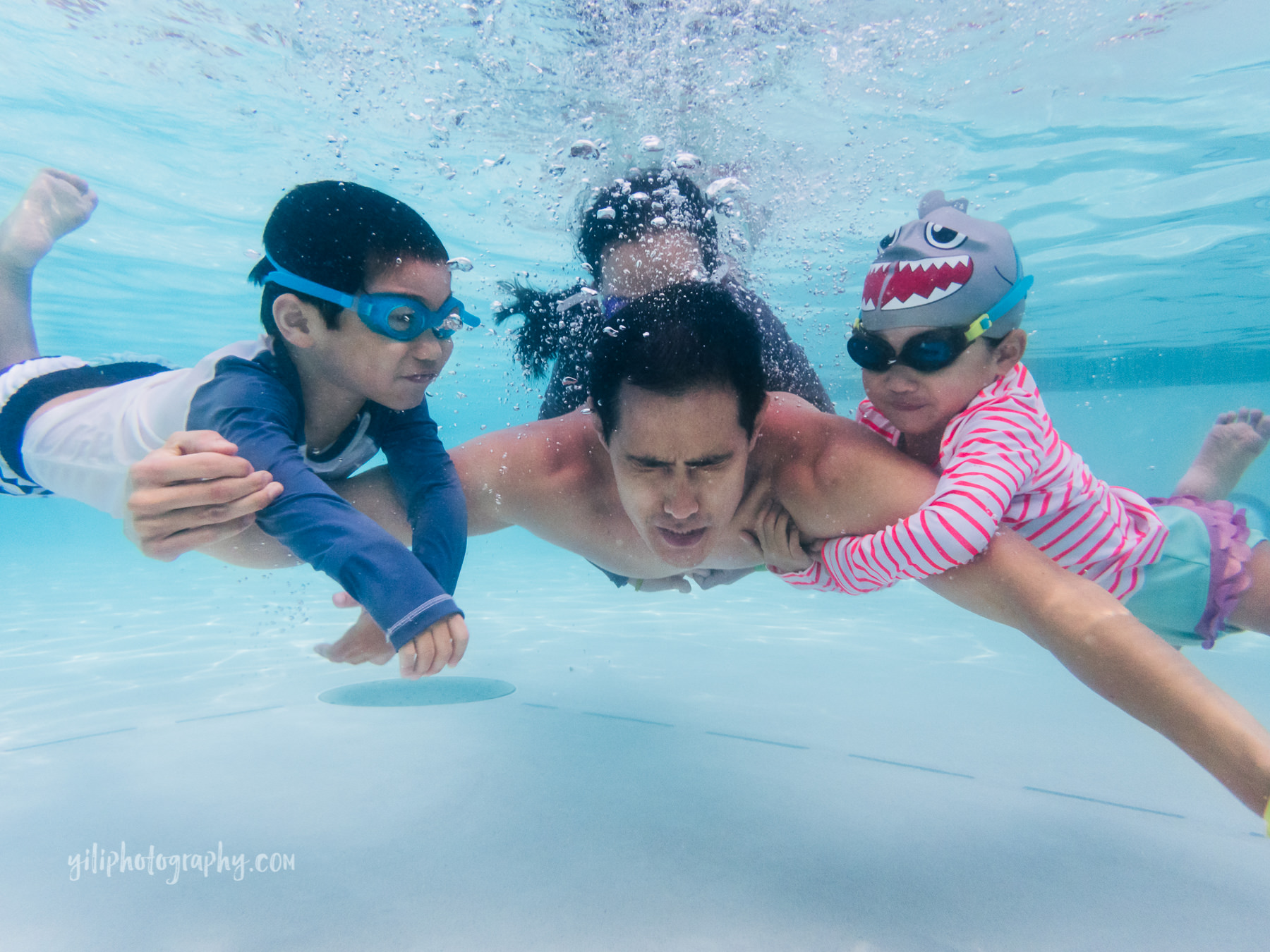 father swimming underwater with three kids holding him