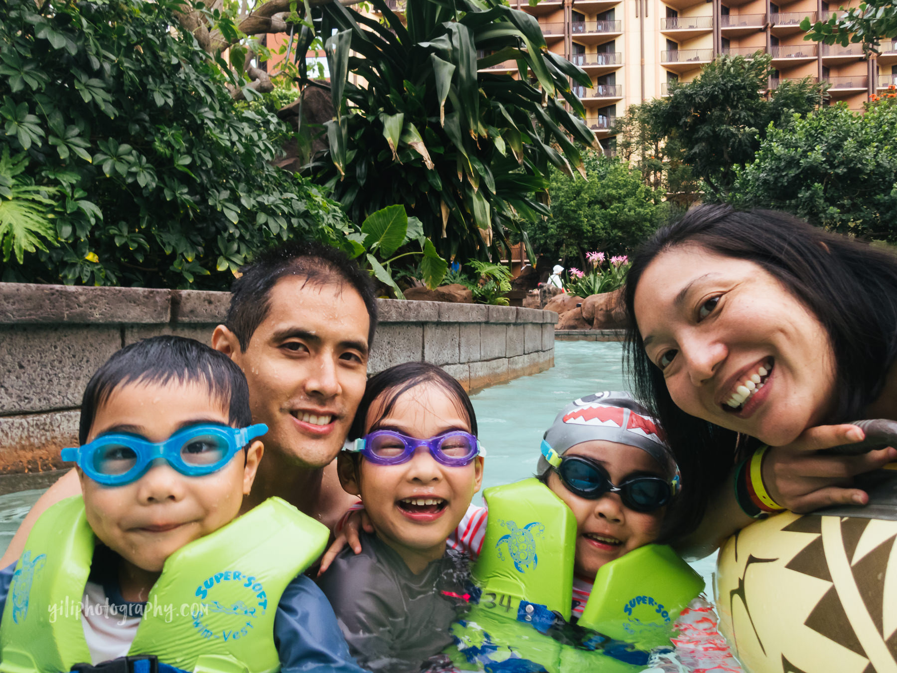 family of five in lazy river at Aulani