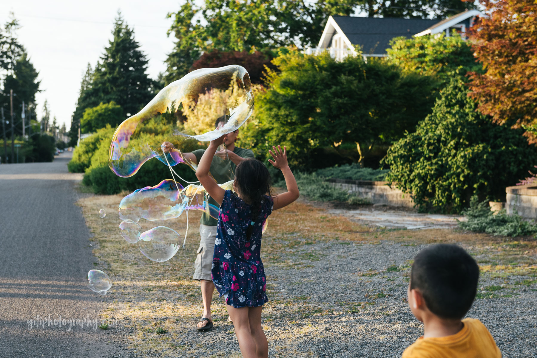 kids running towards dad making giant bubble