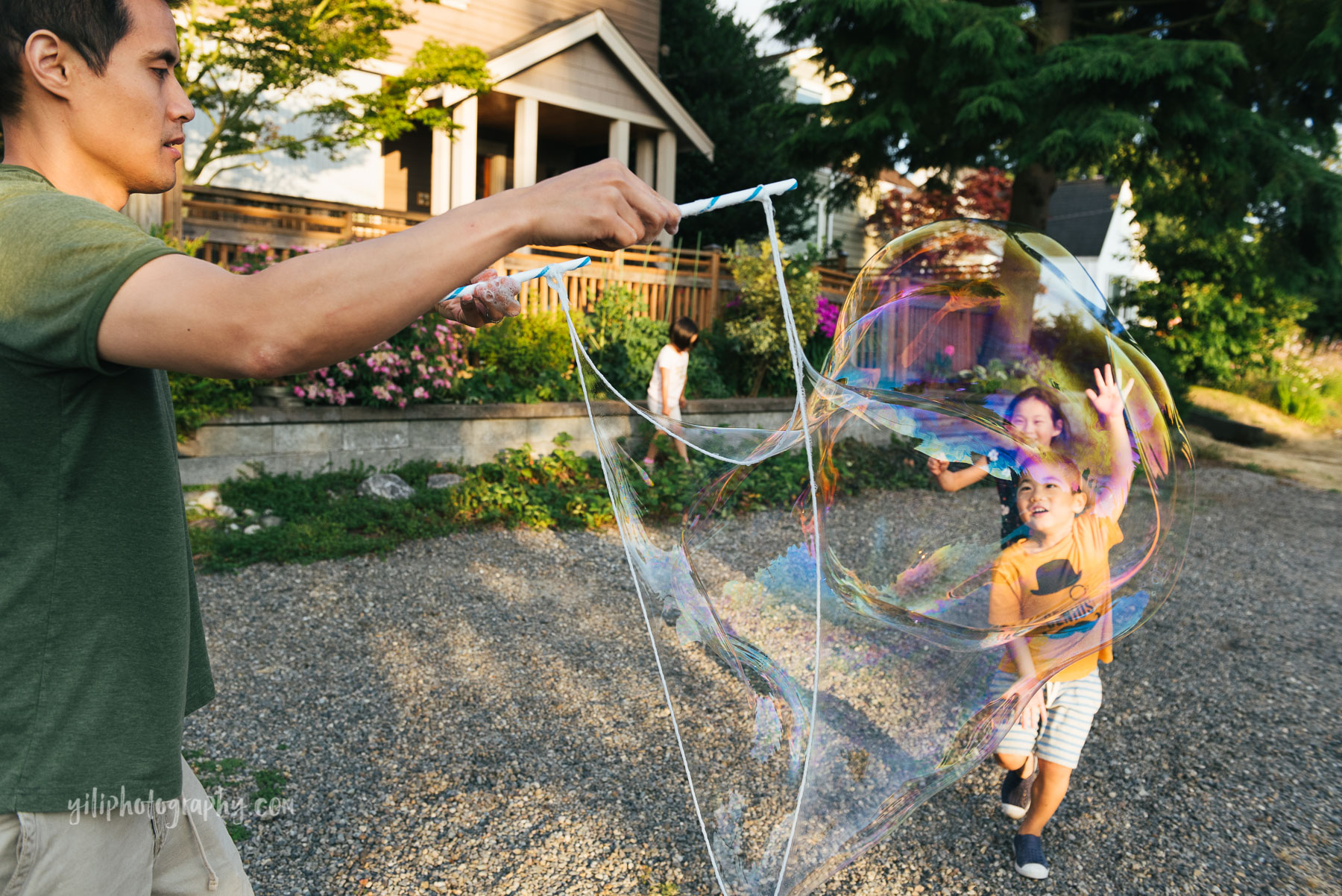 two asian american children running towards giant bubble