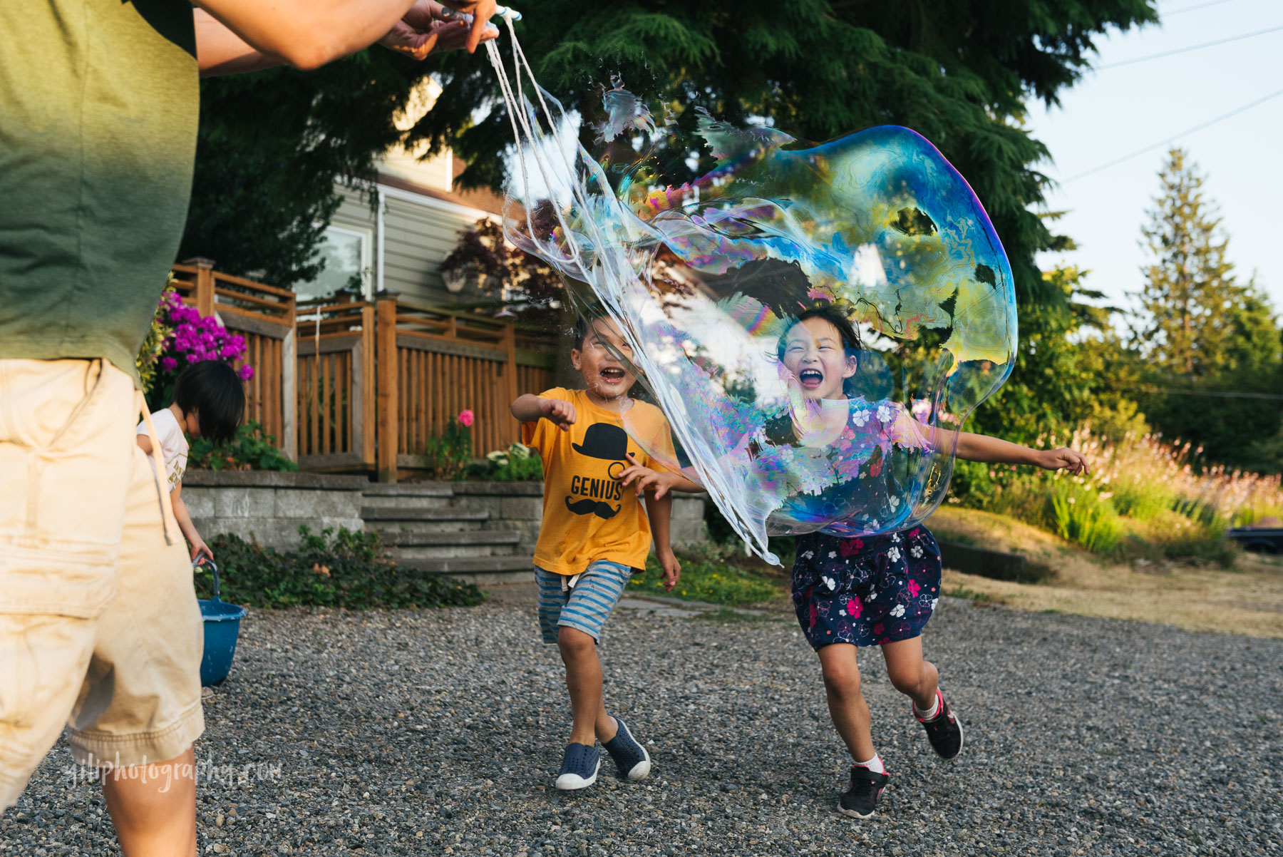 boy and girl running towards giant bubble