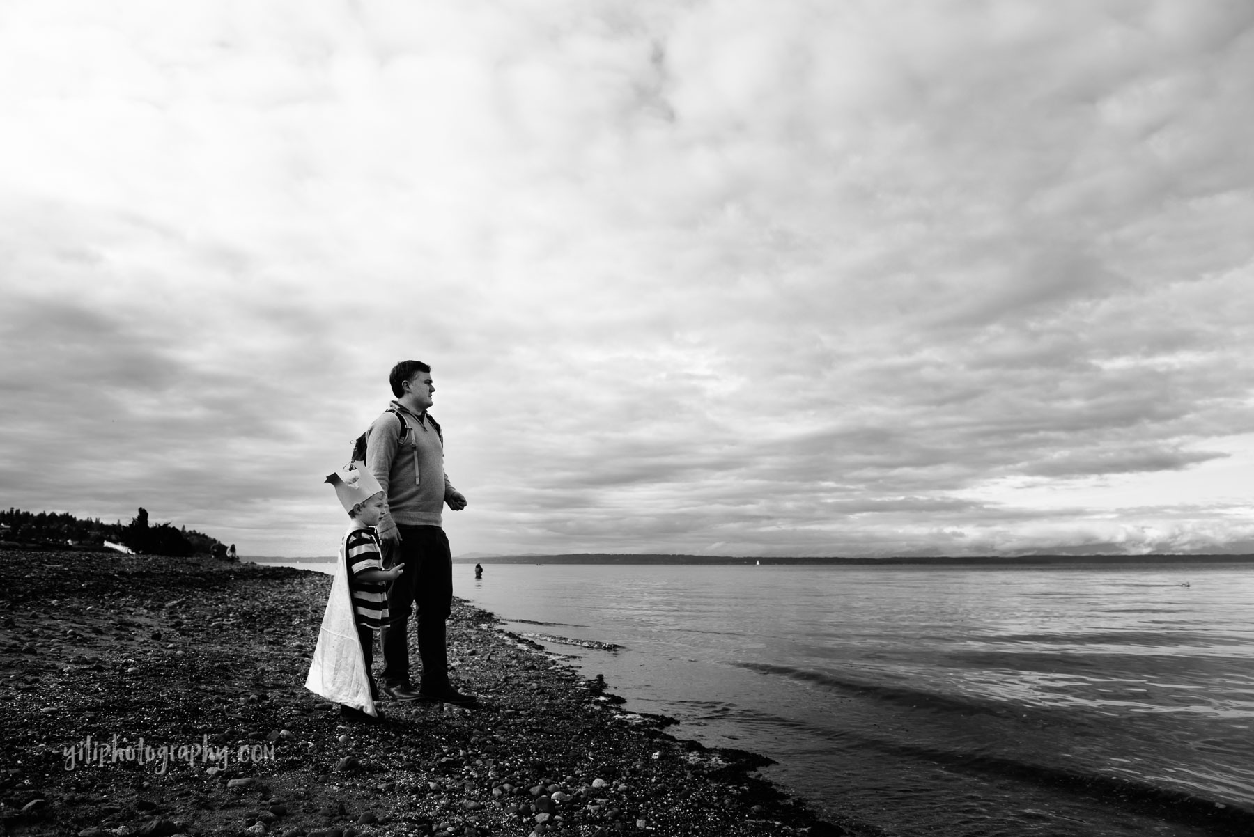 Father and son gazing out at ocean with dramatic clouds