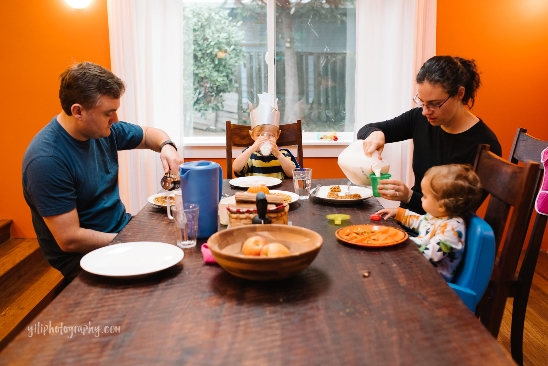 Family of four eating breakfast together at dining table