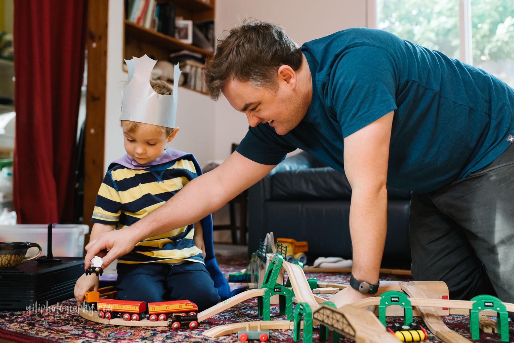 Father building train set with son at home
