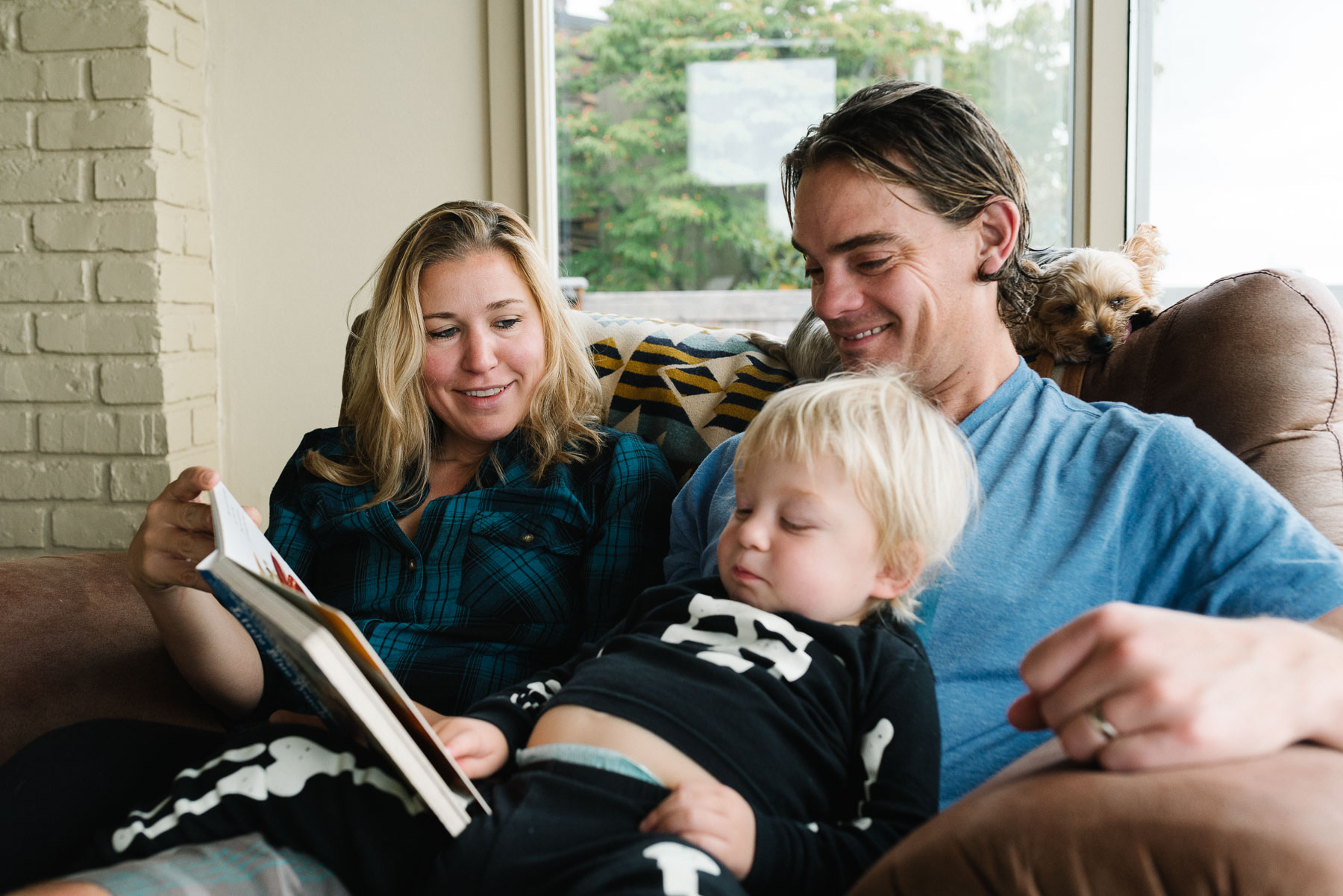 Mom and dad sitting on couch reading to toddler son