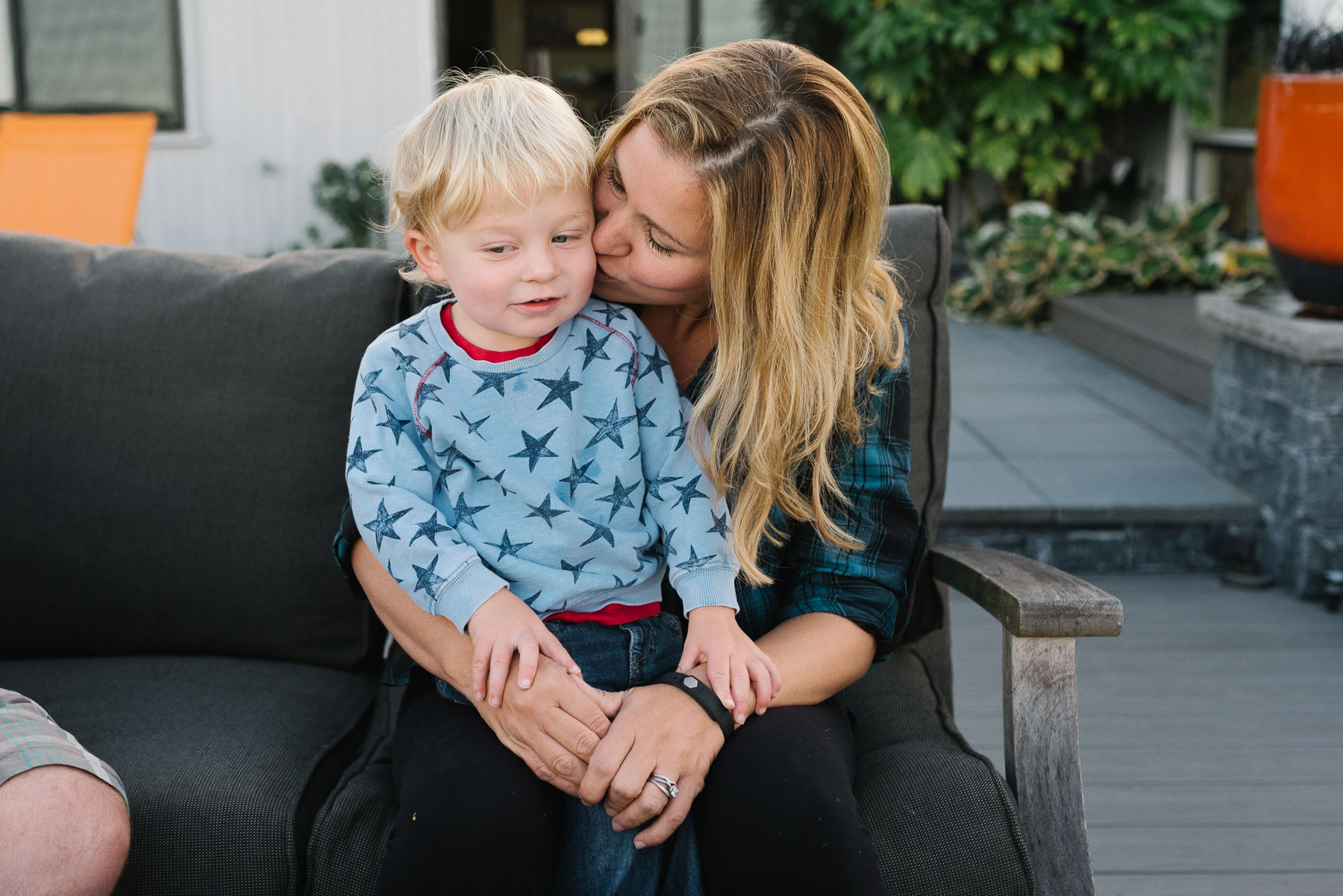 Toddler boy sitting on mom's lap while she kisses his cheek