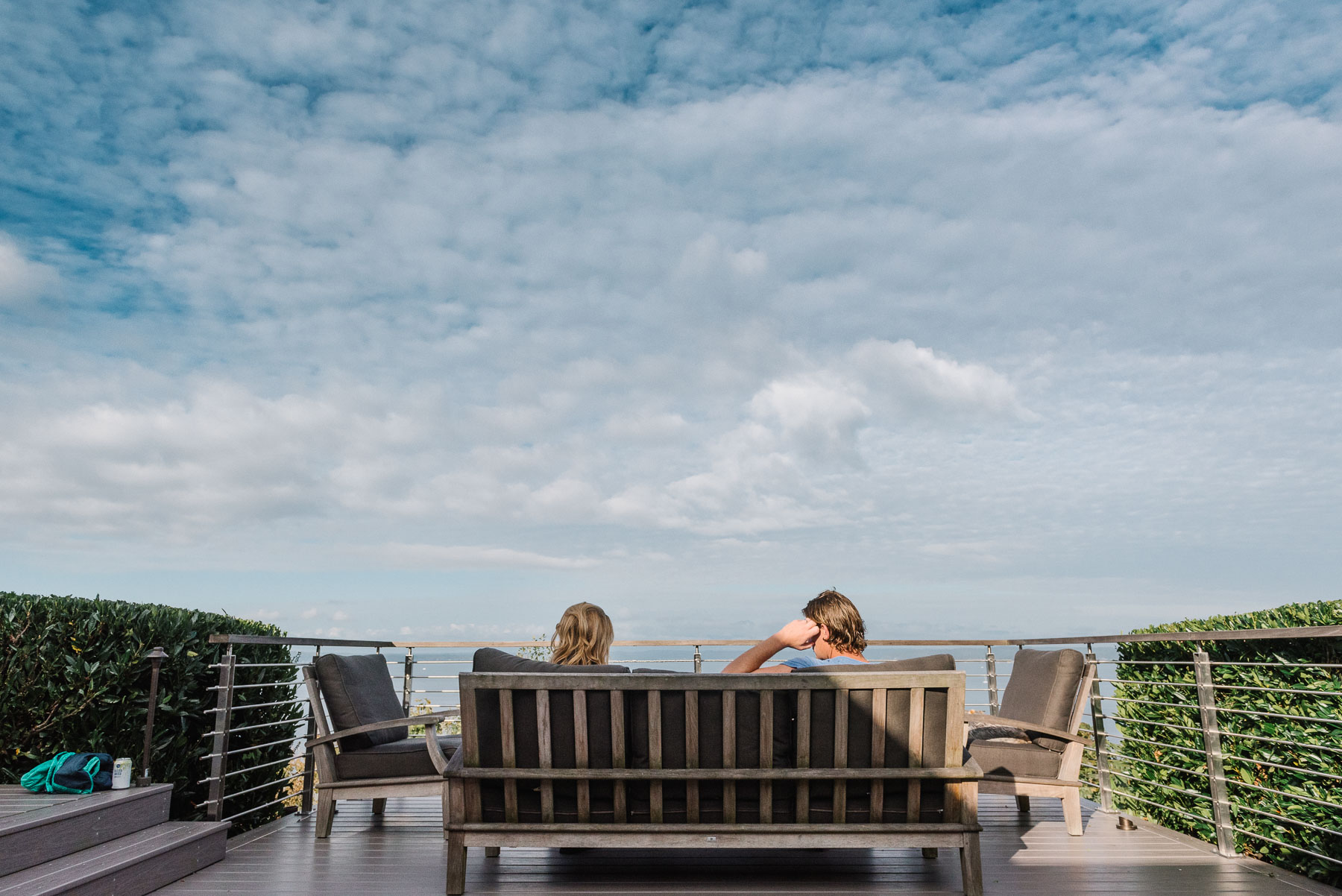 Wide angle view of family sitting on patio furniture outside on sunny day overlooking ocean