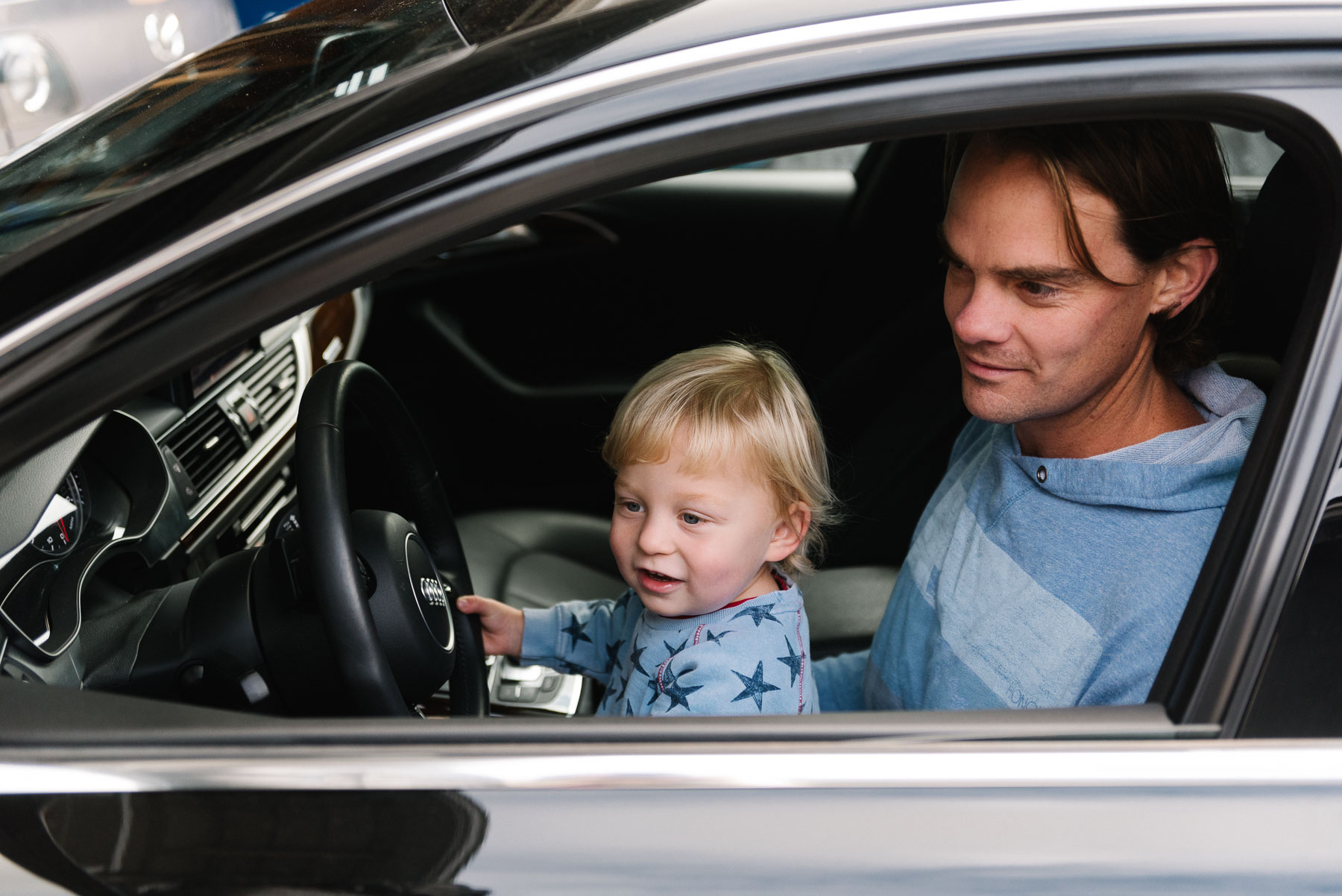 Toddler boy sitting on dad's lap in drivers seat of car