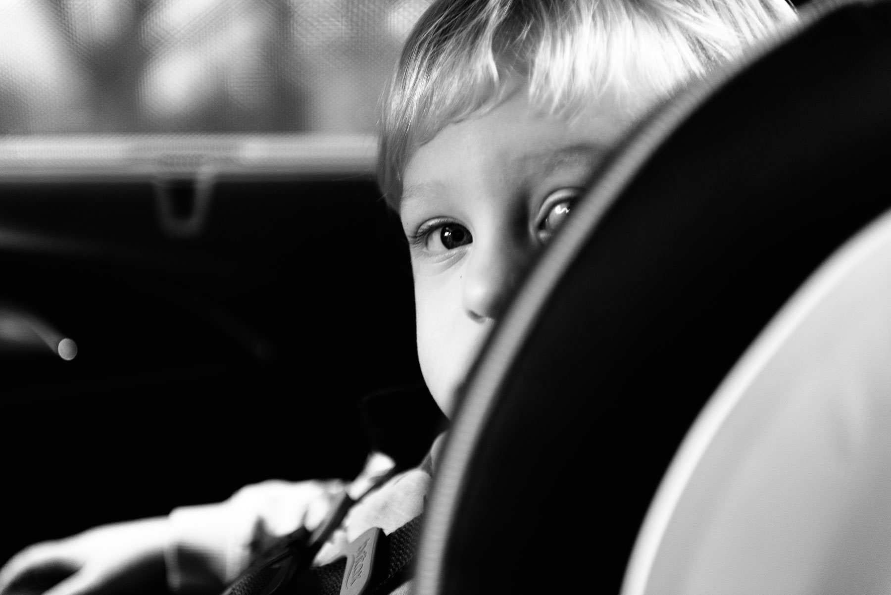 Toddler boy peeking over side of carseat