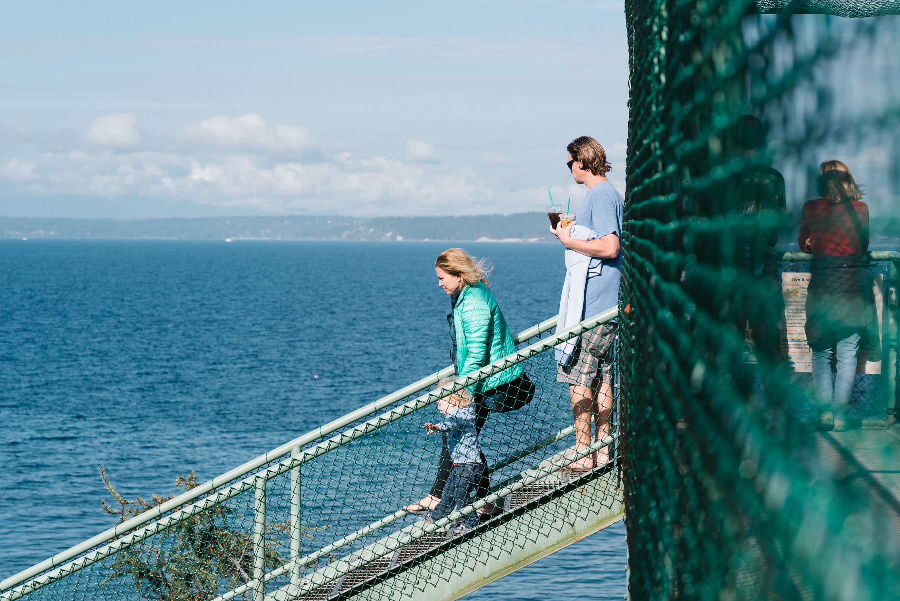 Family walking down train trestle bridge at Carkeek Park in Seattle