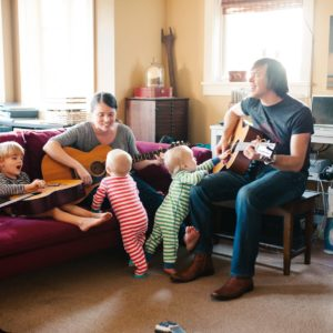 Mom and dad playing guitars and singing with twins and older son in living room