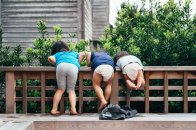 three kids leaning over wooden fence