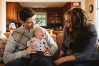 Mom and dad smiling laughing with baby boy in living room
