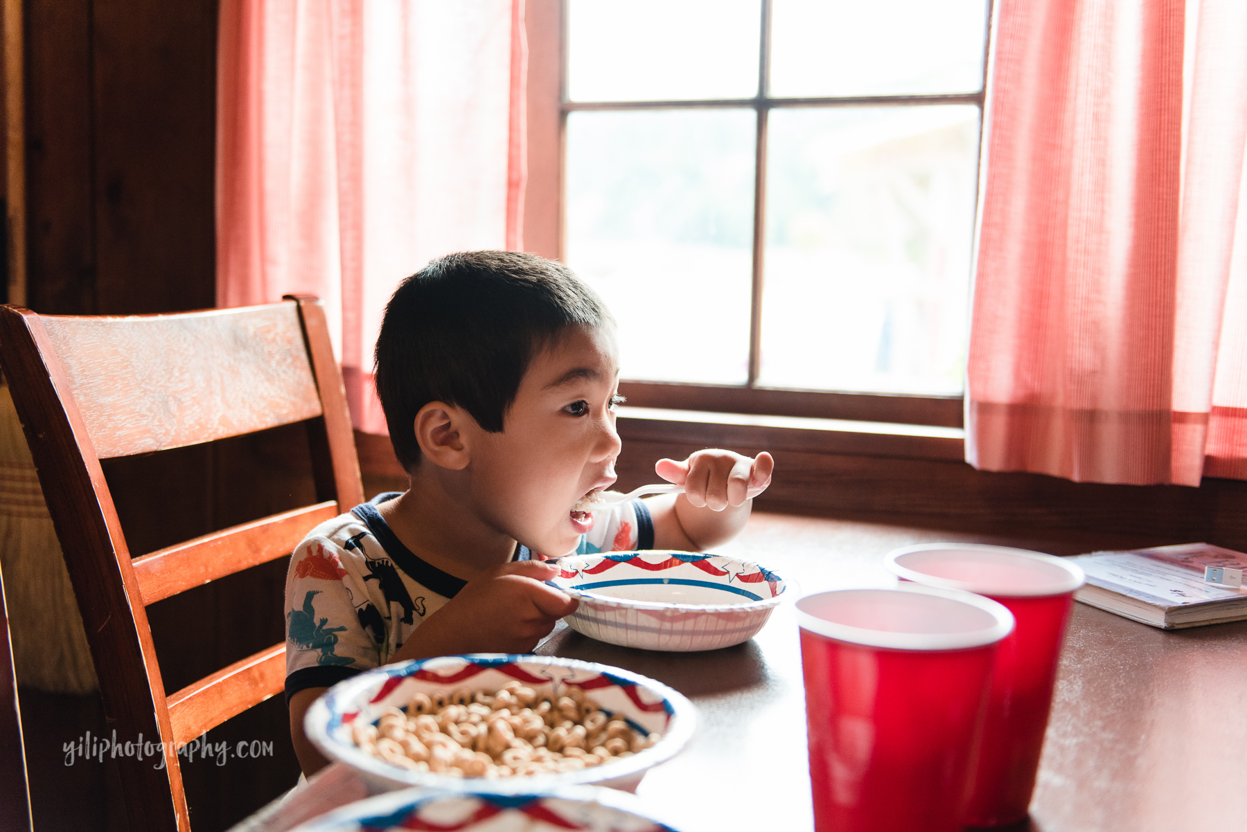 seattle boy eating breakfast inside cabin at cama beach state park