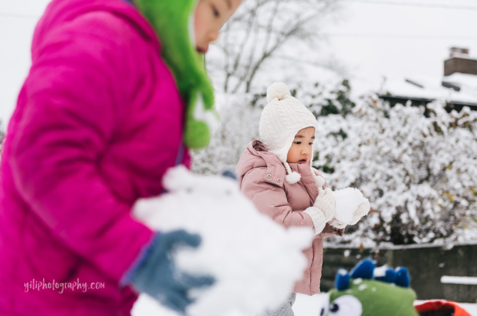 seattle little girl holding snowball with big sister in foreground