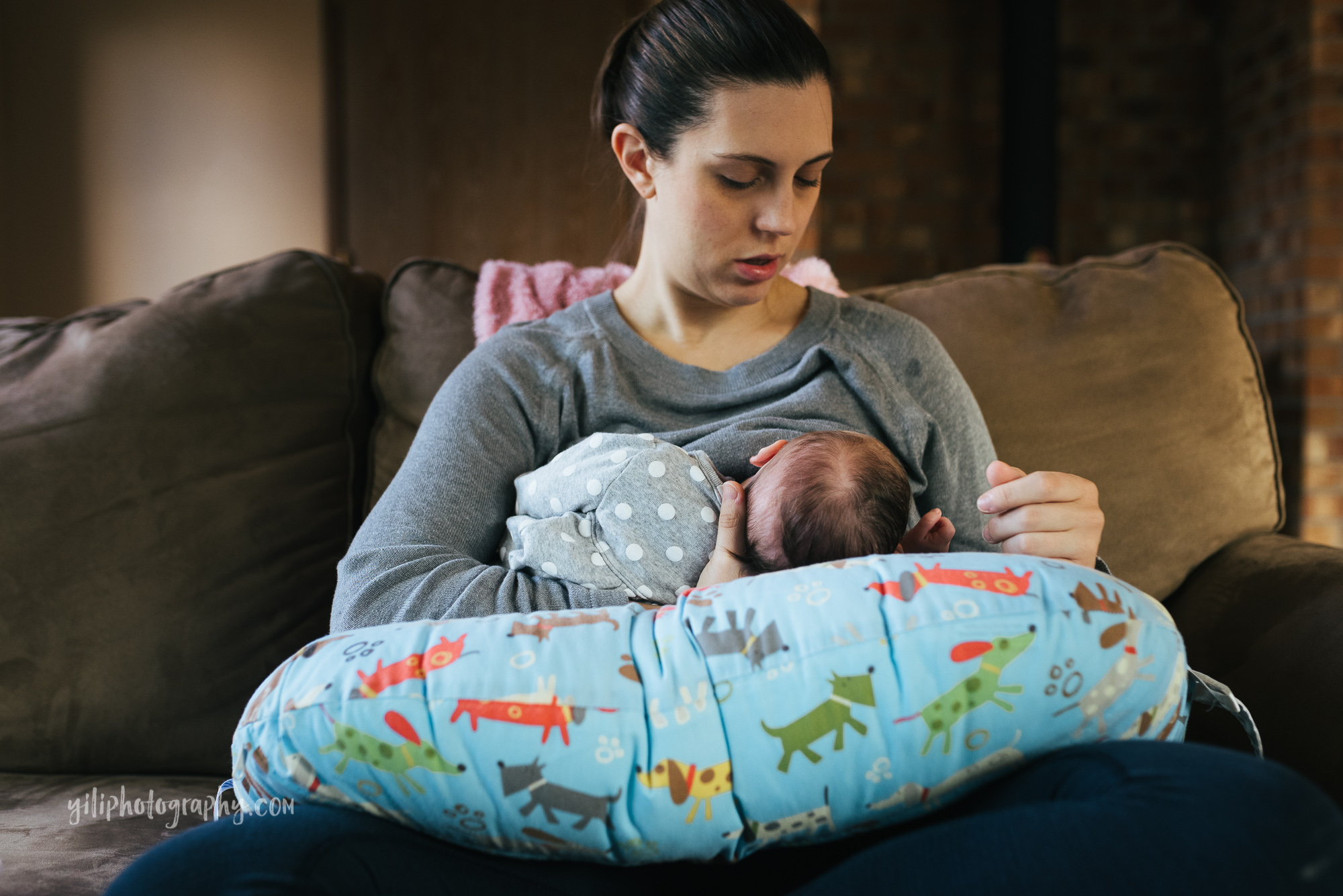 seattle mom sitting on couch nursing newborn baby