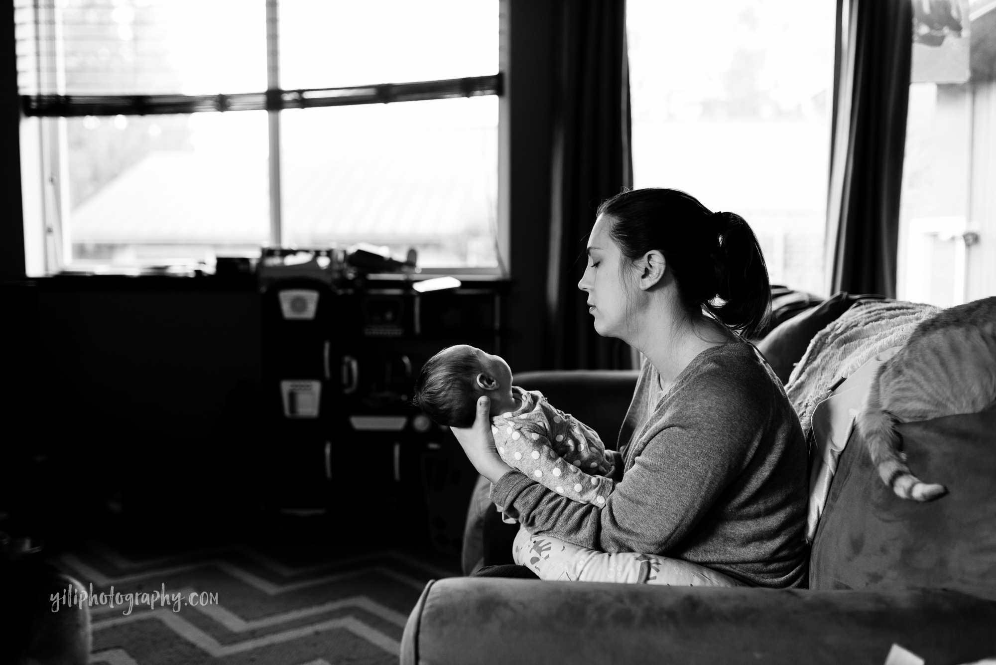 black and white photo of seattle mom with newborn on couch
