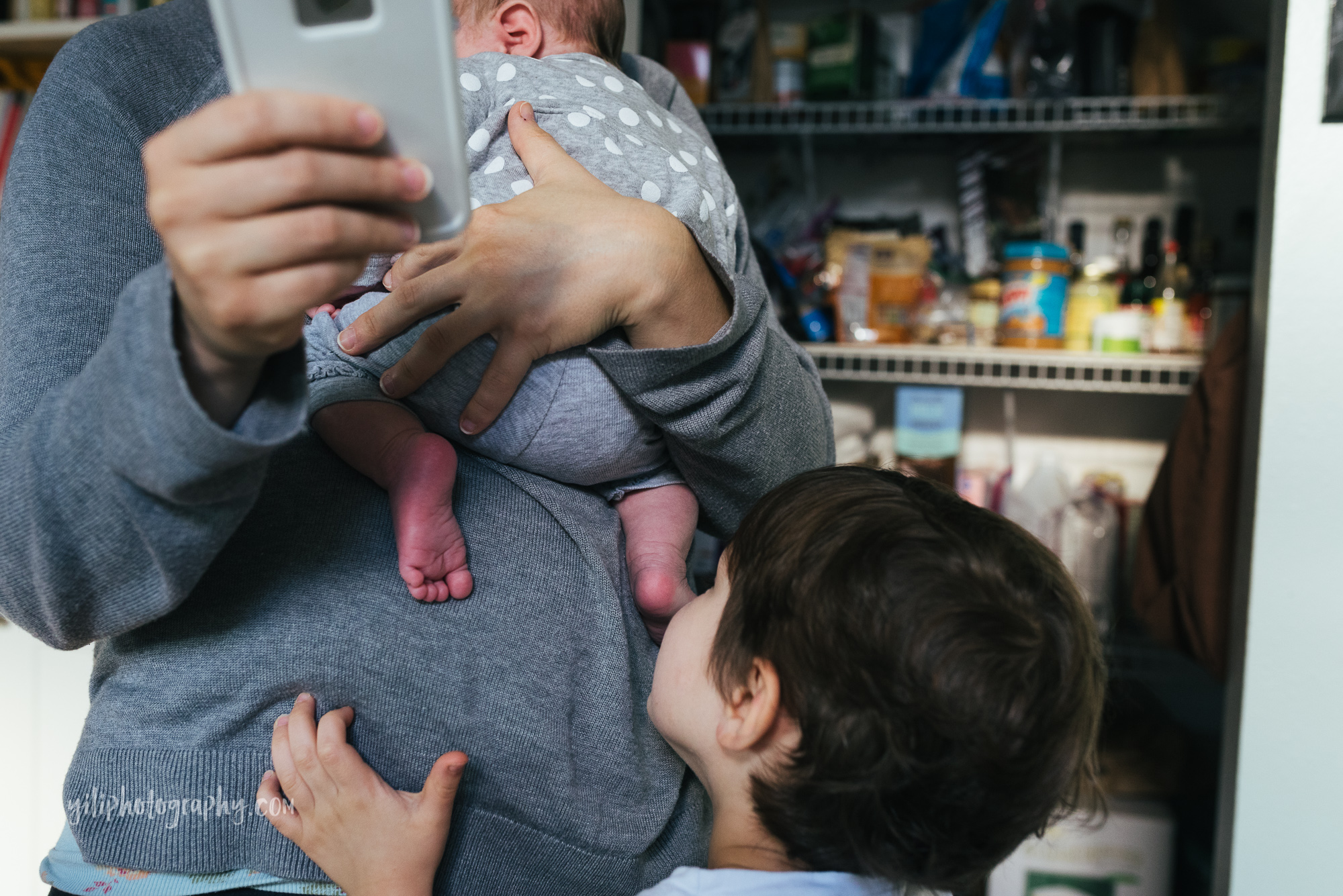 seattle mom checking smartphone while holding newborn girl
