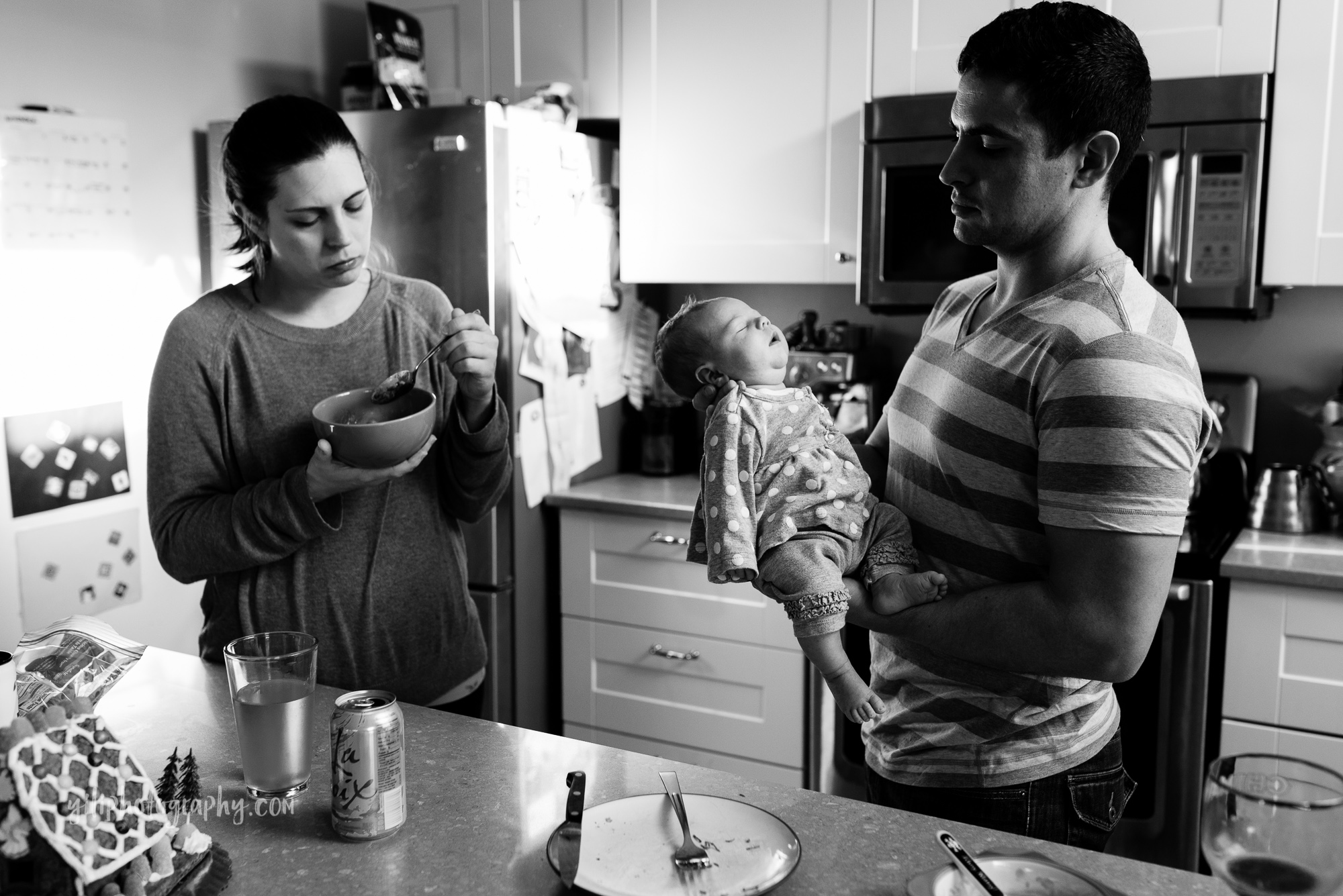 seattle mom eating quick lunch while husband holds newborn baby