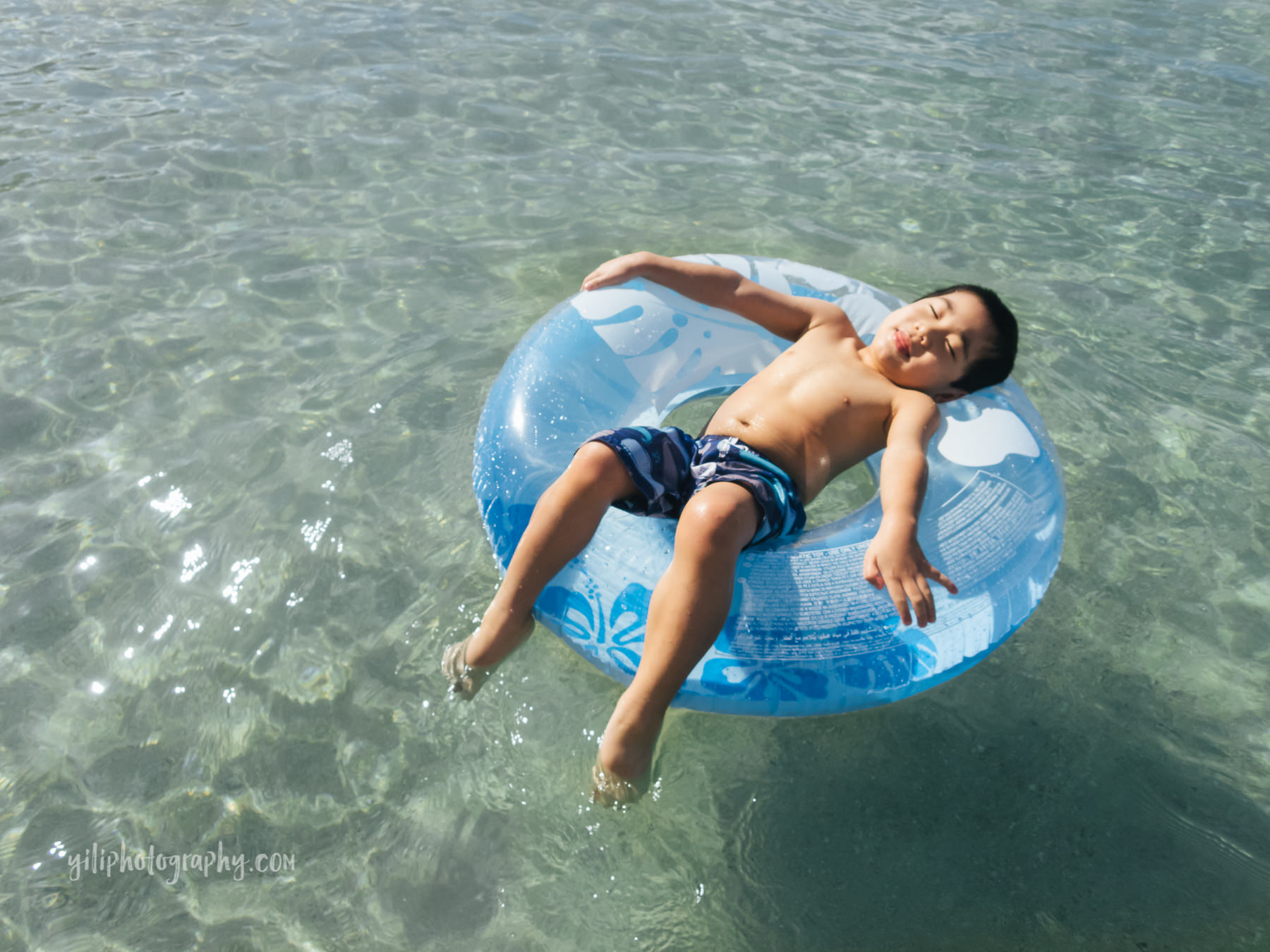 little boy floating in inner tube at beach