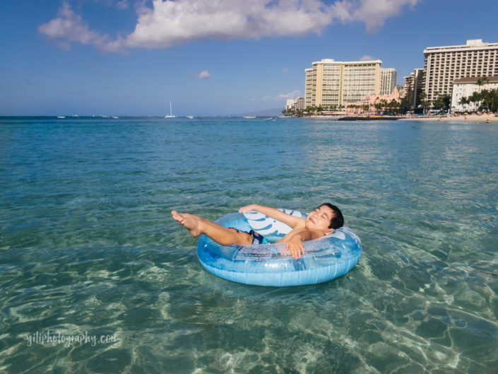 boy in inner tube at waikiki beach