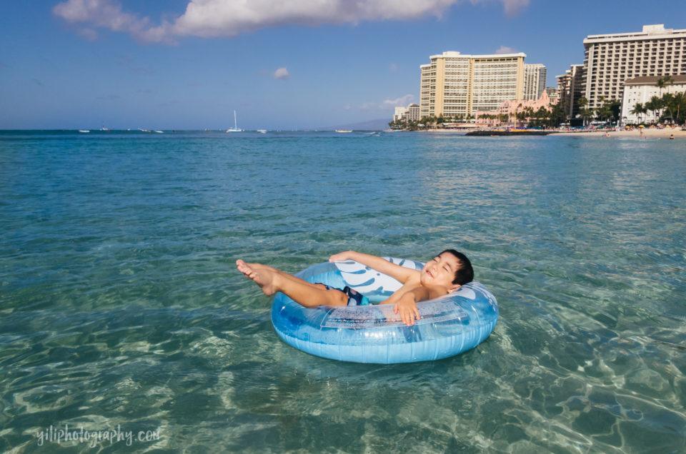 boy in inner tube at waikiki beach
