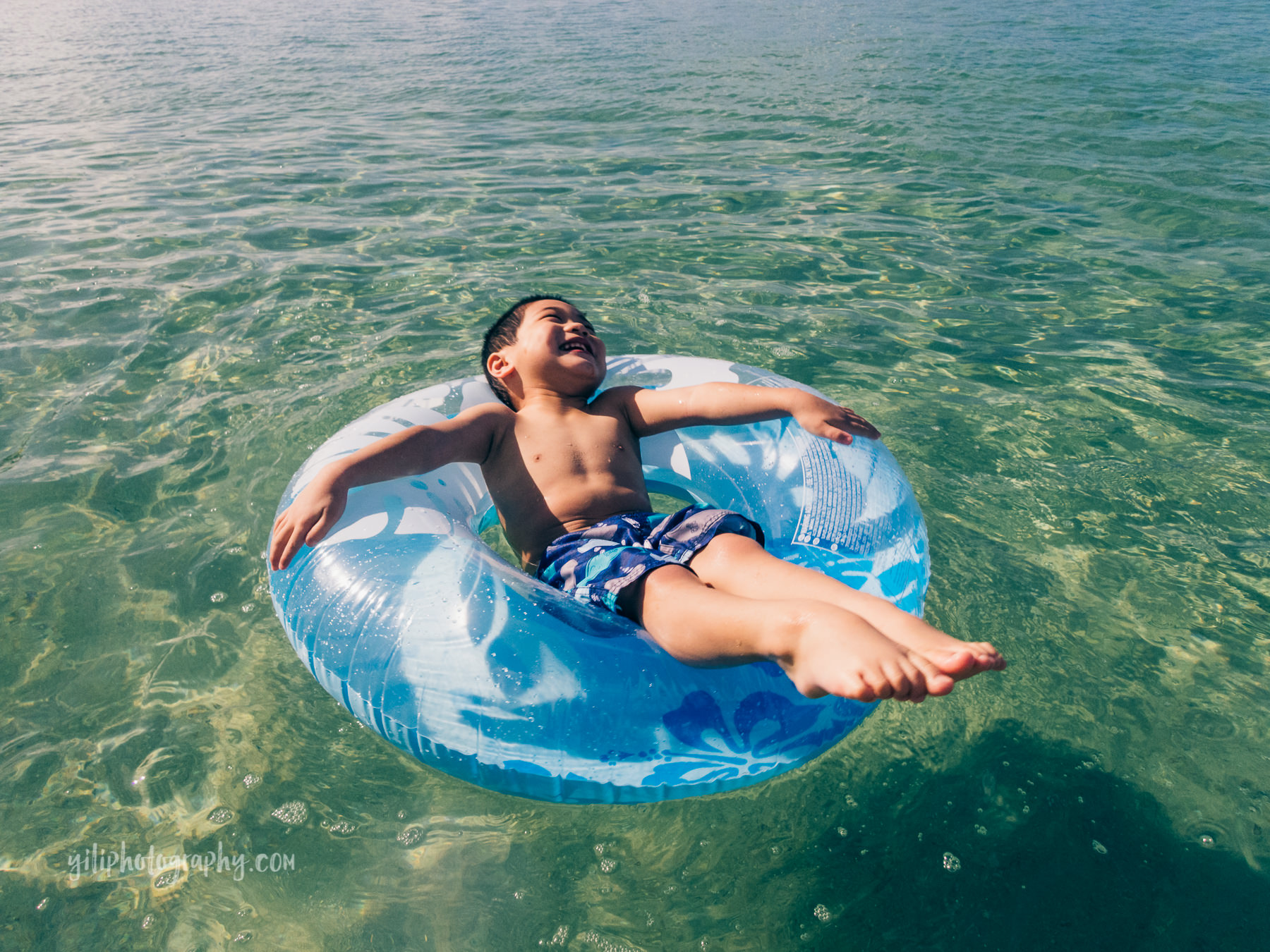 toddler boy laughing in floatie in ocean