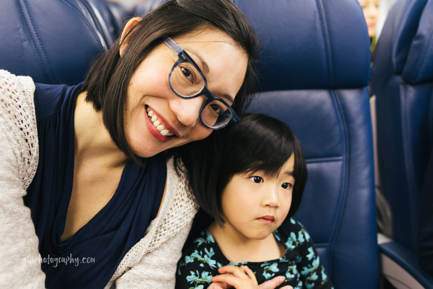 mom and daughter on airplane together