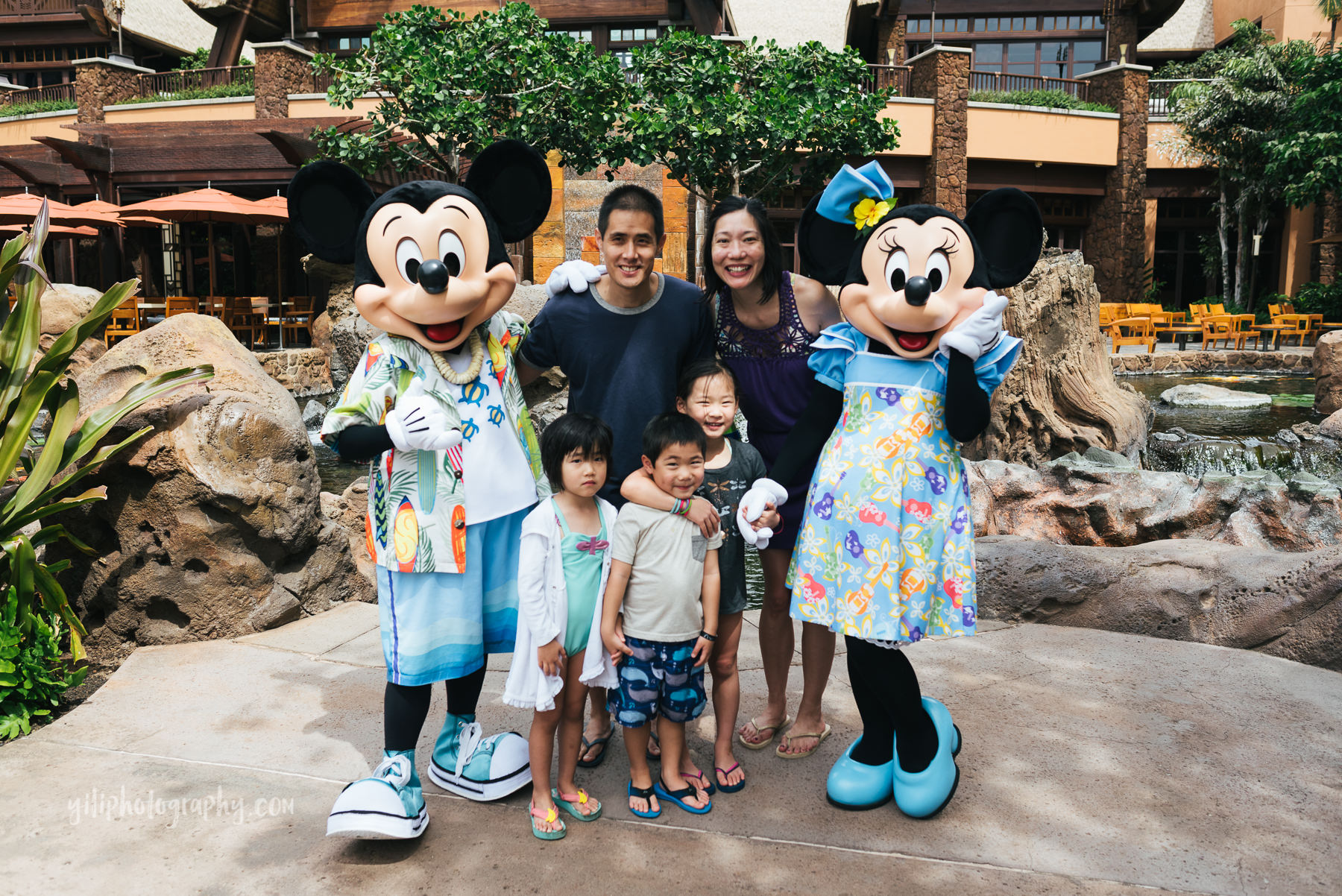 family posing with mickey and minnie at disney aulani