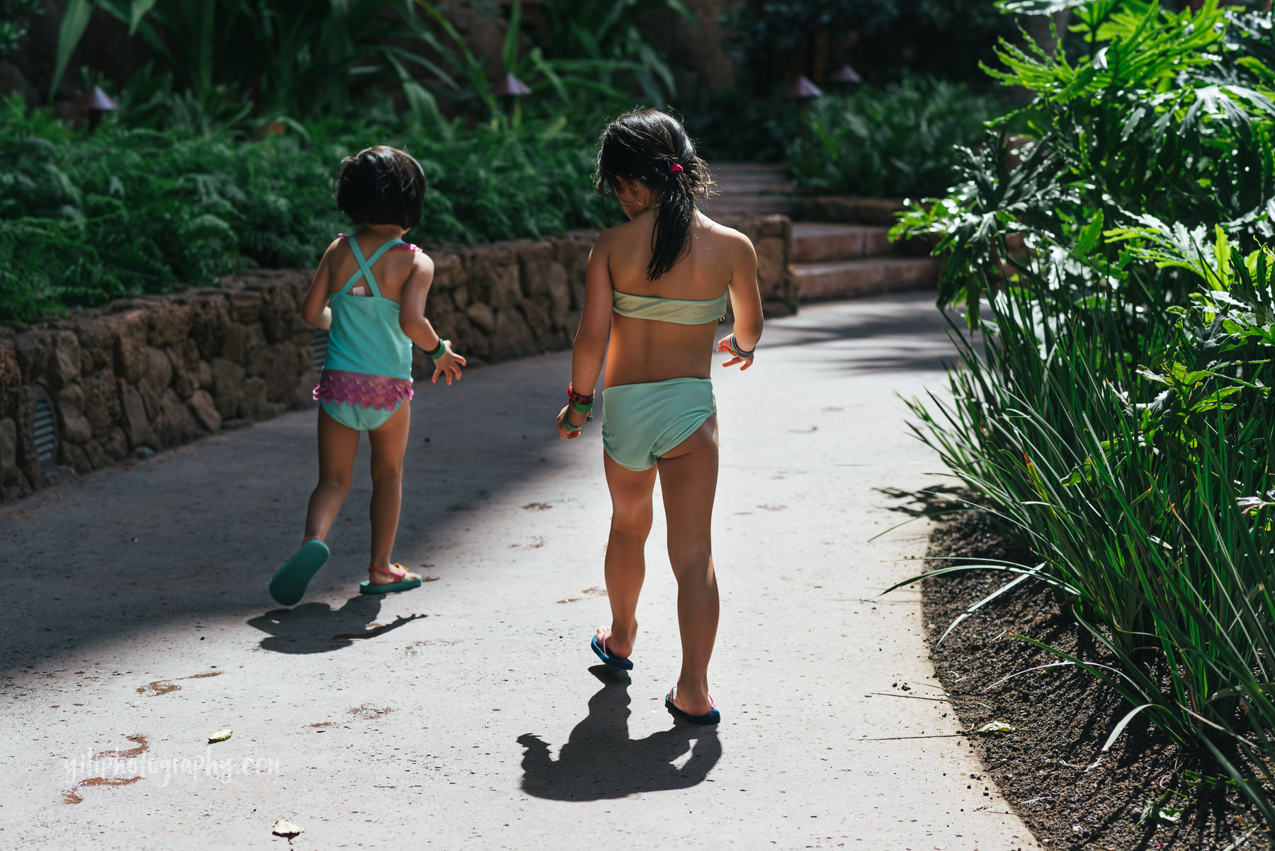 two girls walking along path in swimsuits