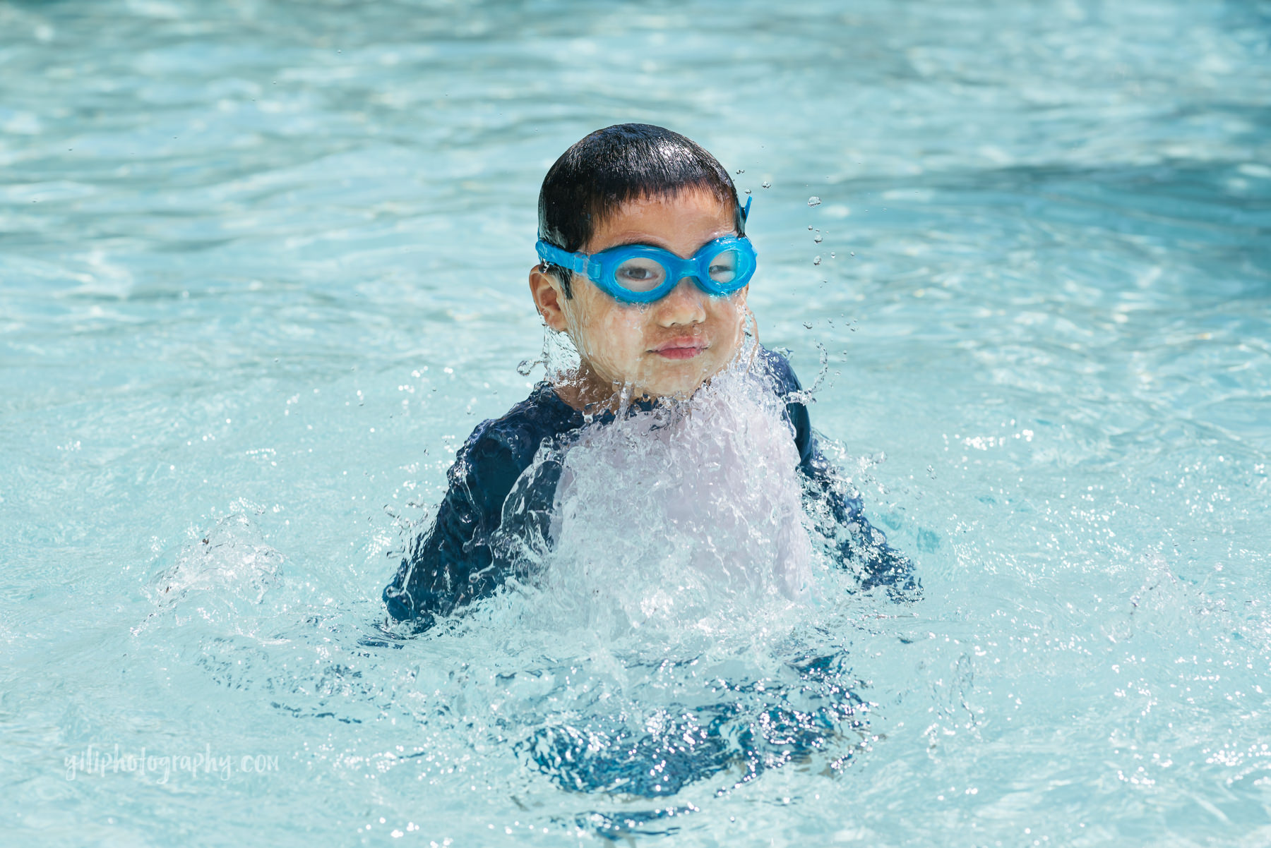boy with water dripping off face in pool