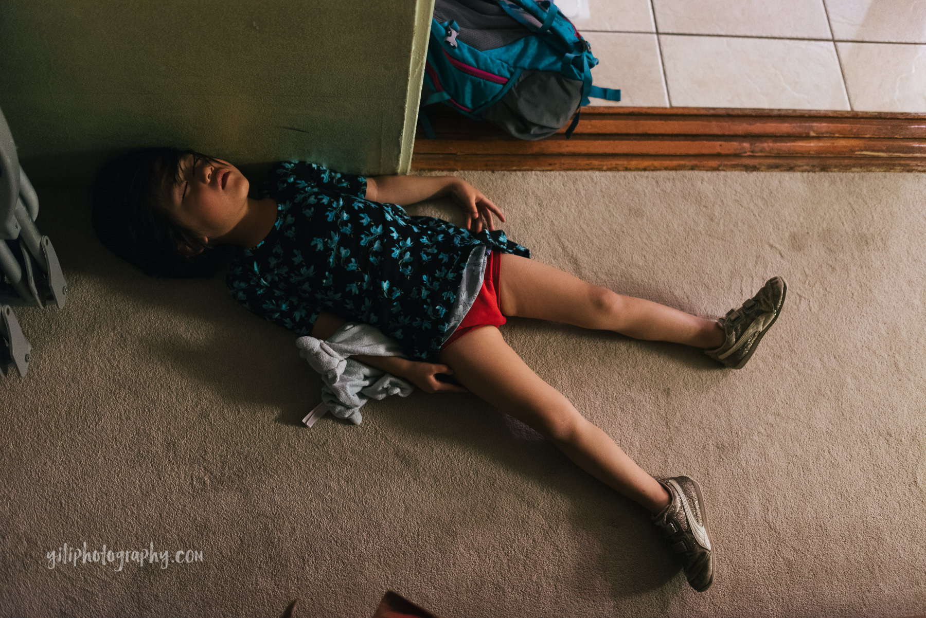little girl asleep on floor of hotel