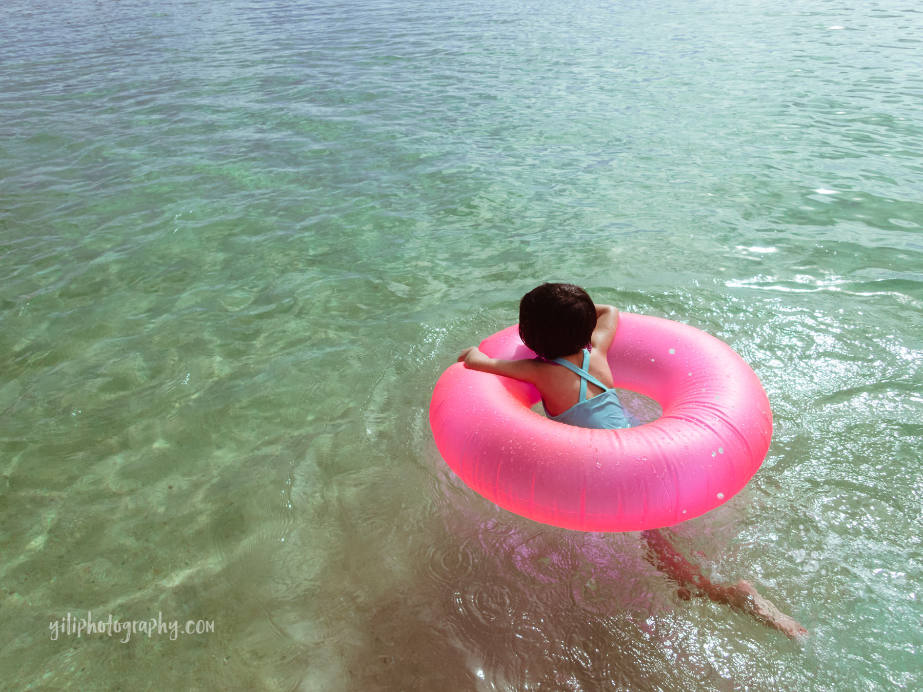 toddler in inner tube at beach
