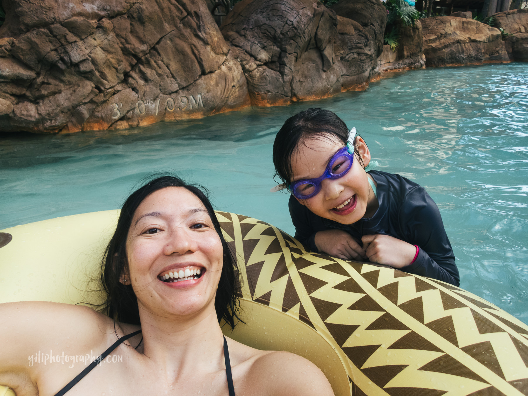 mom in inner tube with daughter in lazy river
