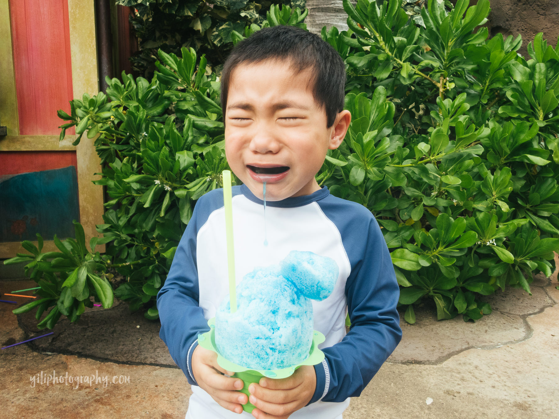 boy holding shave ice crying