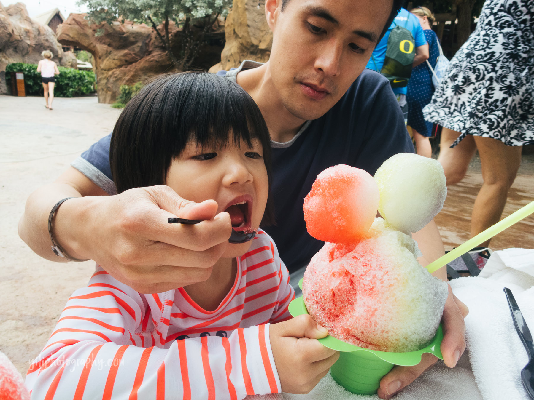 father feeding little girl shave ice